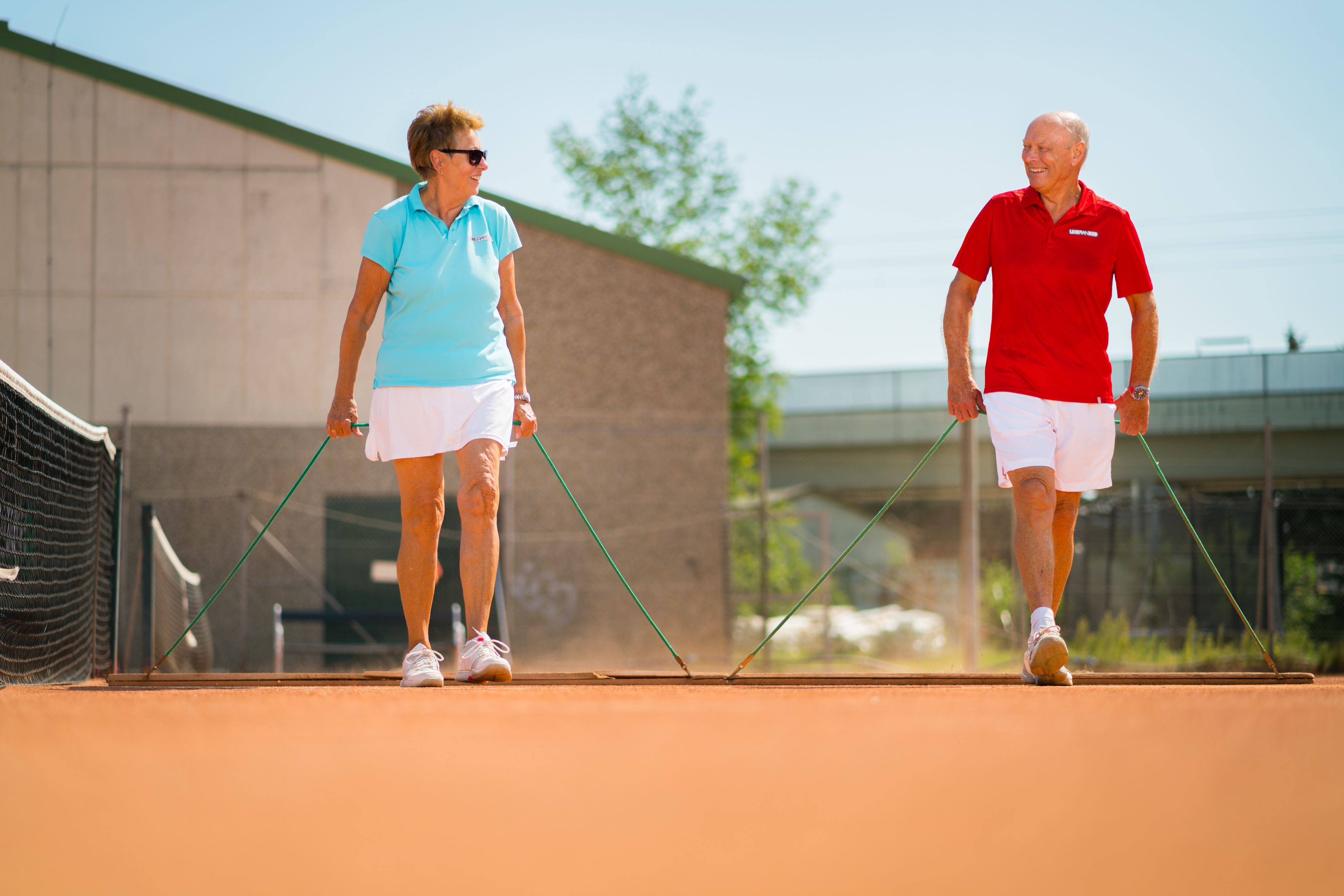 A retired couple prepares to play tennis