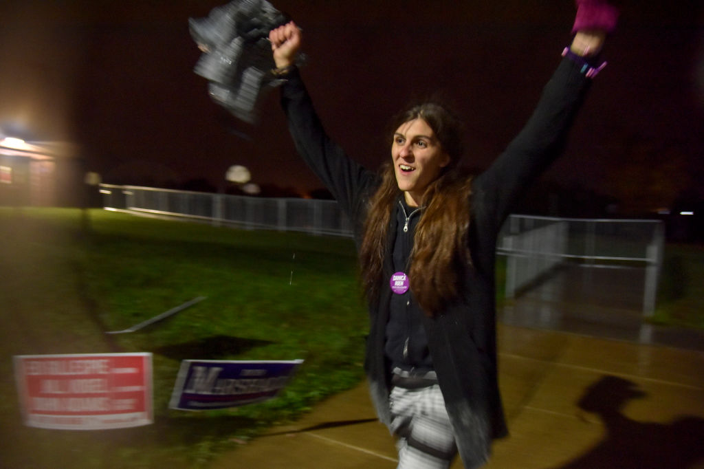 Danica Roem raises her arms in celebration after winning her election