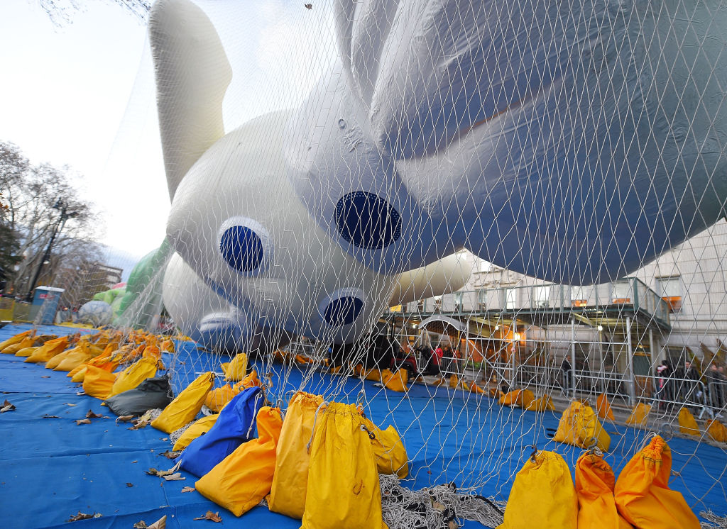 Pillsbury Doughboy balloon for Macy's Thanksgiving Day Parade is inflated and contained by a net