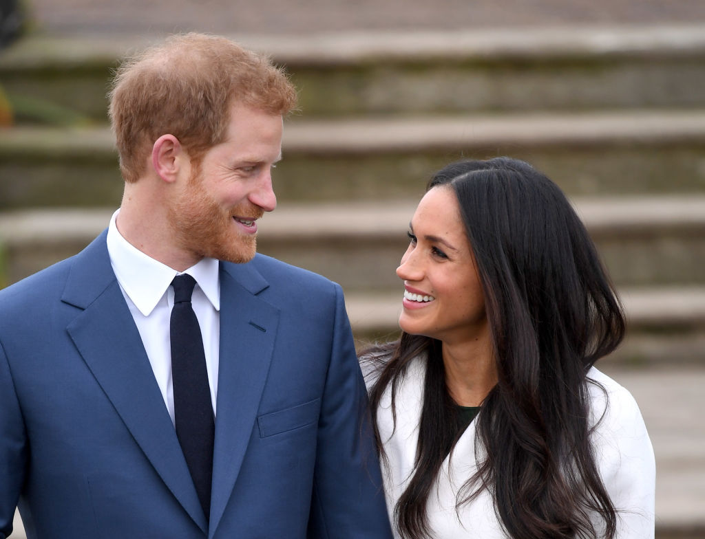 Prince Harry and Meghan Markle stand side by side, looking at one another, at official engagement photocall