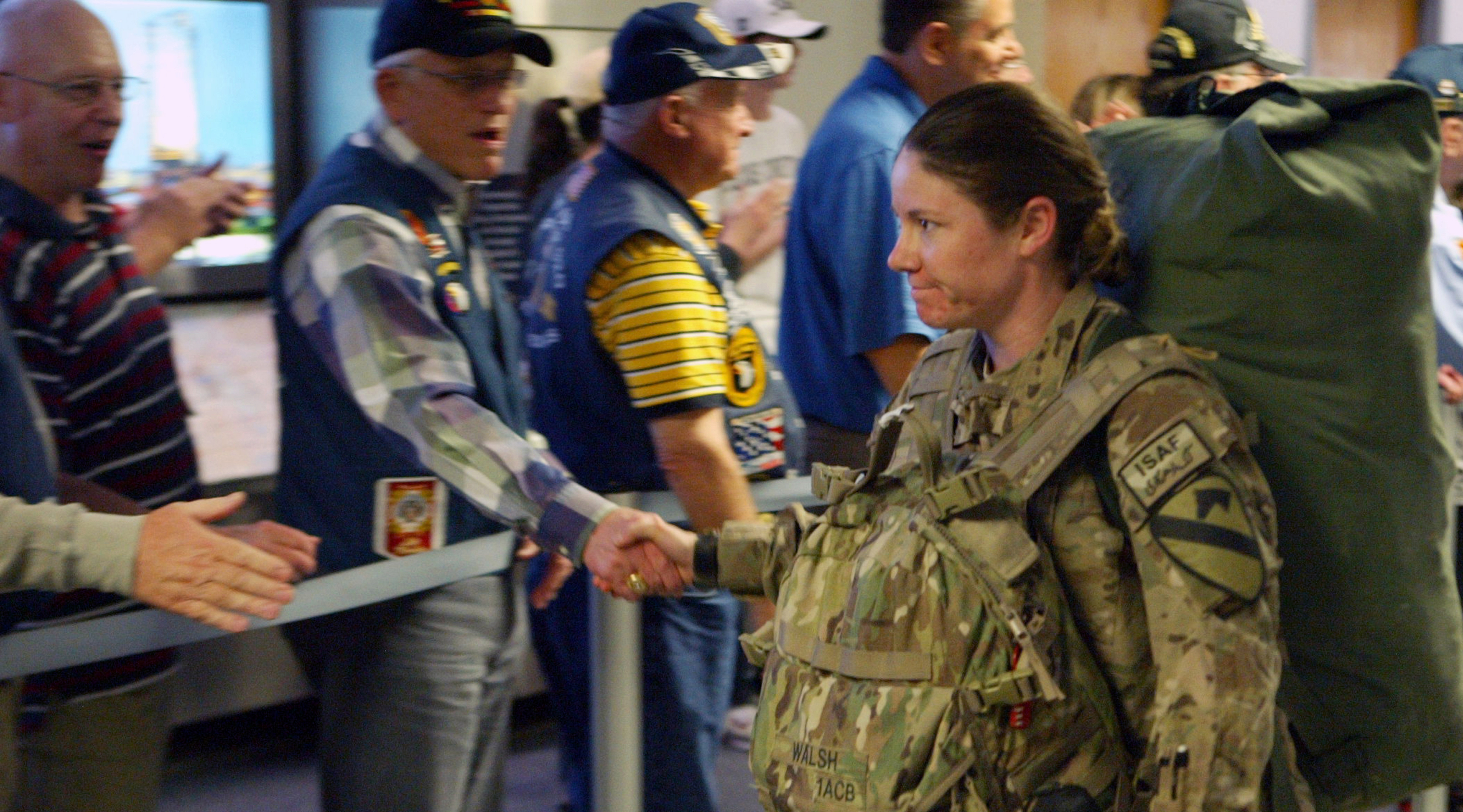 Female soldier shakes hands with older veteran onlookers at DFW International Airport