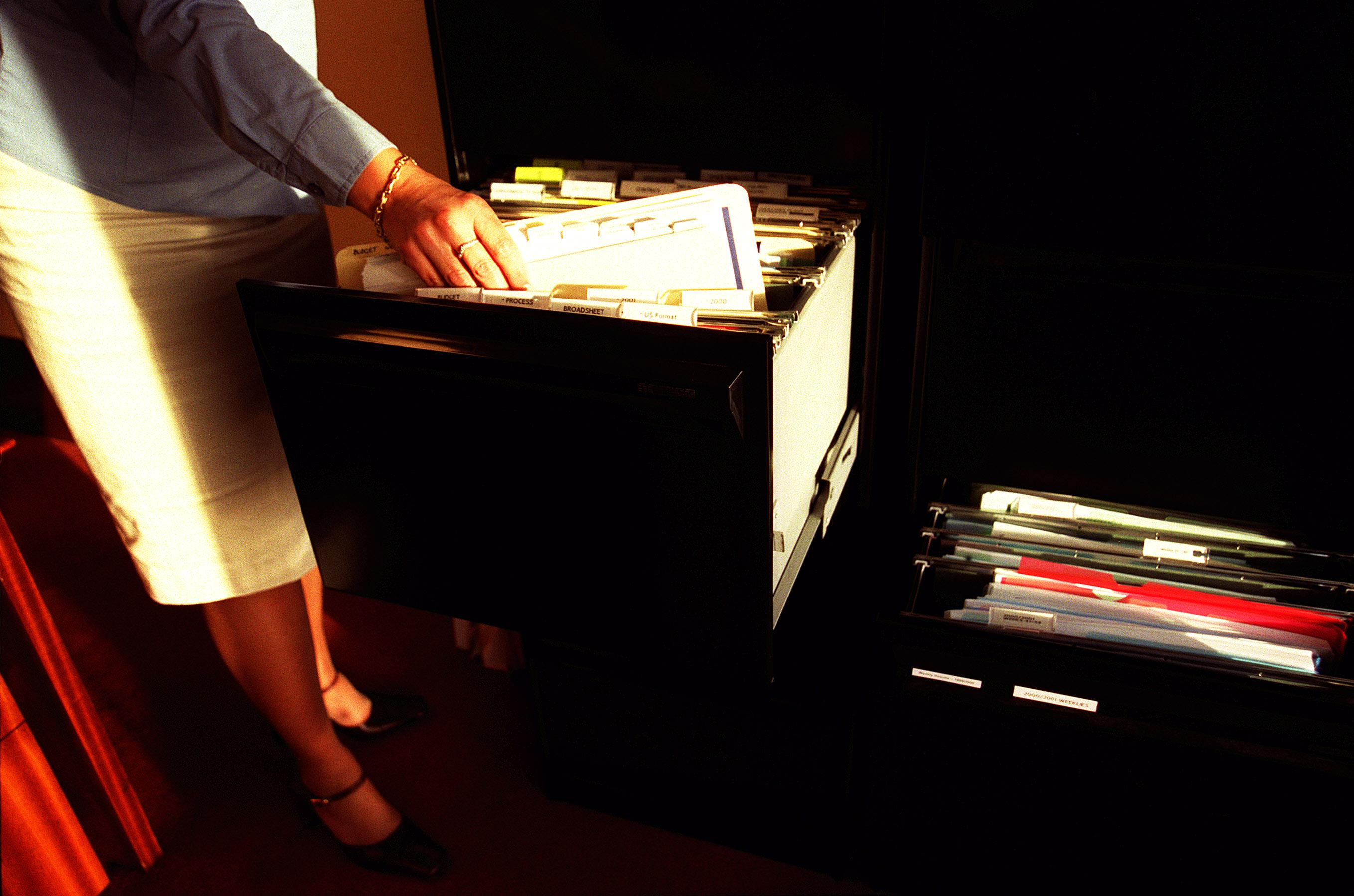 Generic woman taking files out of a filing cabinet in an office, 16 April 2002.