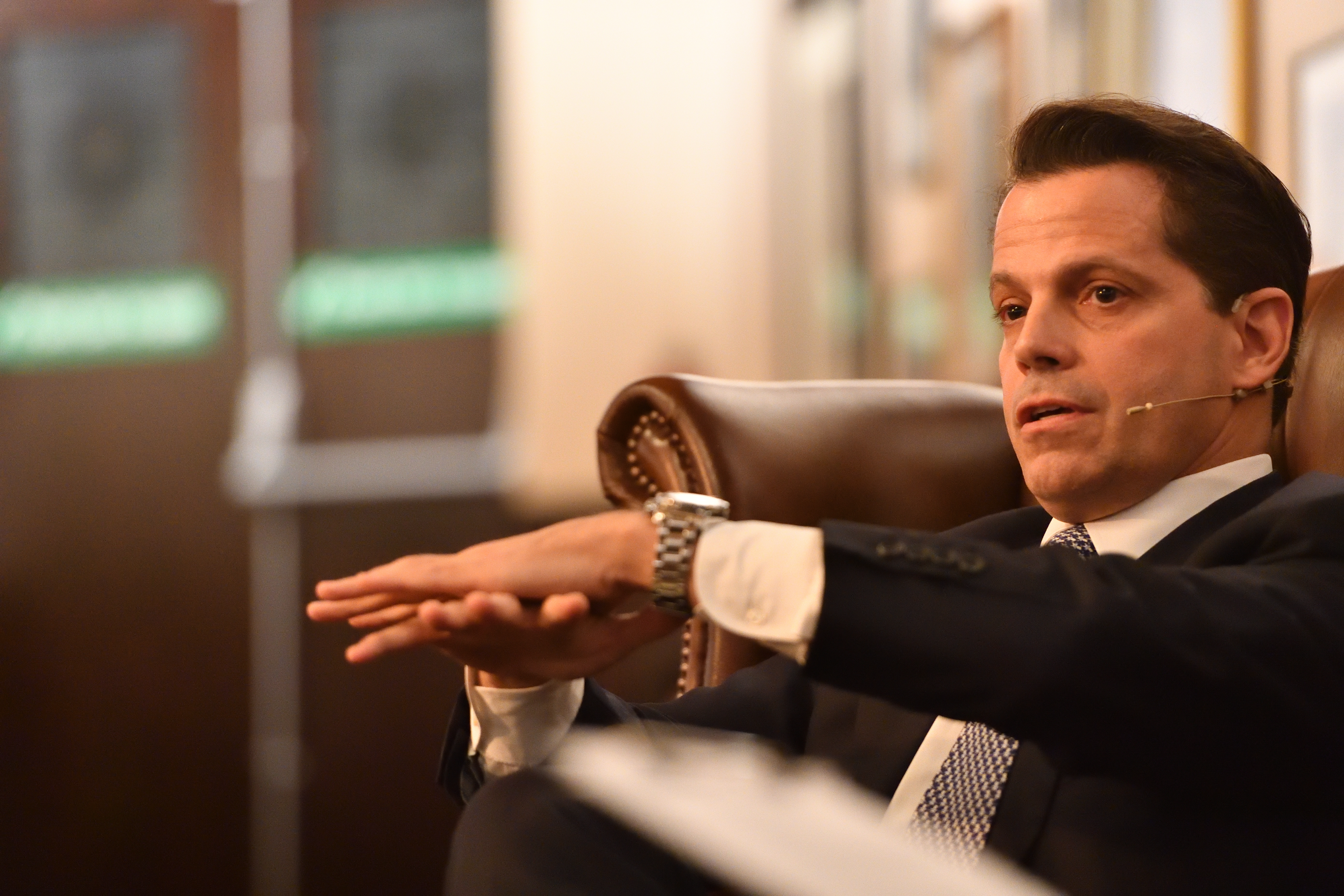 Anthony Scaramucci extends his hands while seated at the Cambridge Union