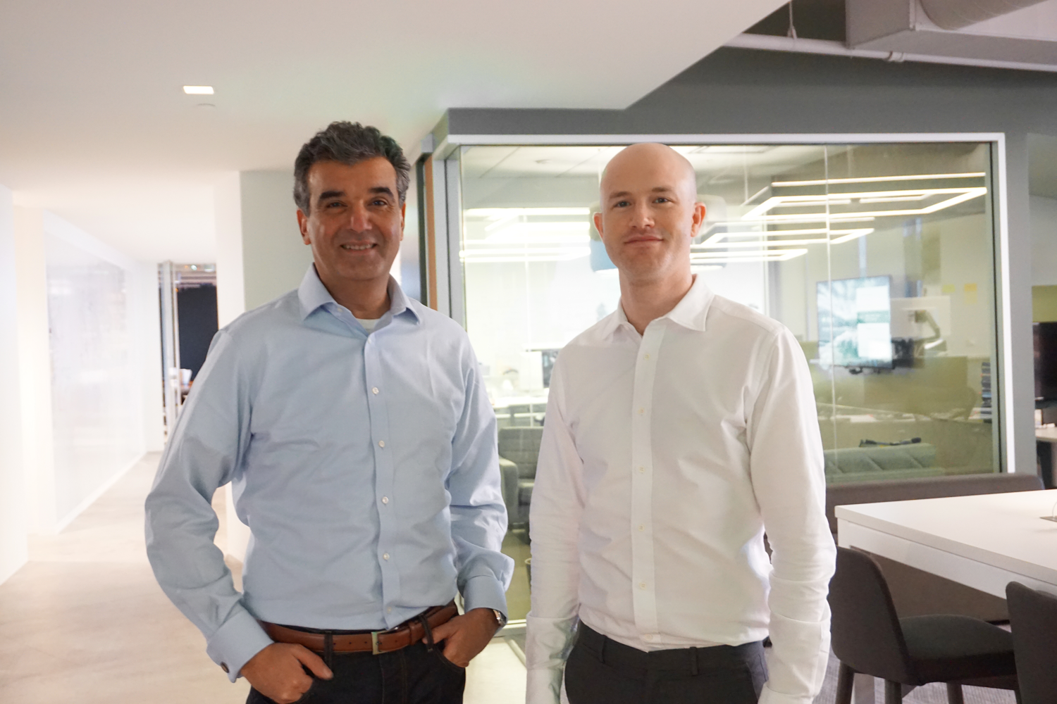 Coinbase CEO and founder Brian Armstrong (right) stands beside new-hire Asiff Hirji (left), a former top executive at TD Ameritrade and HP.