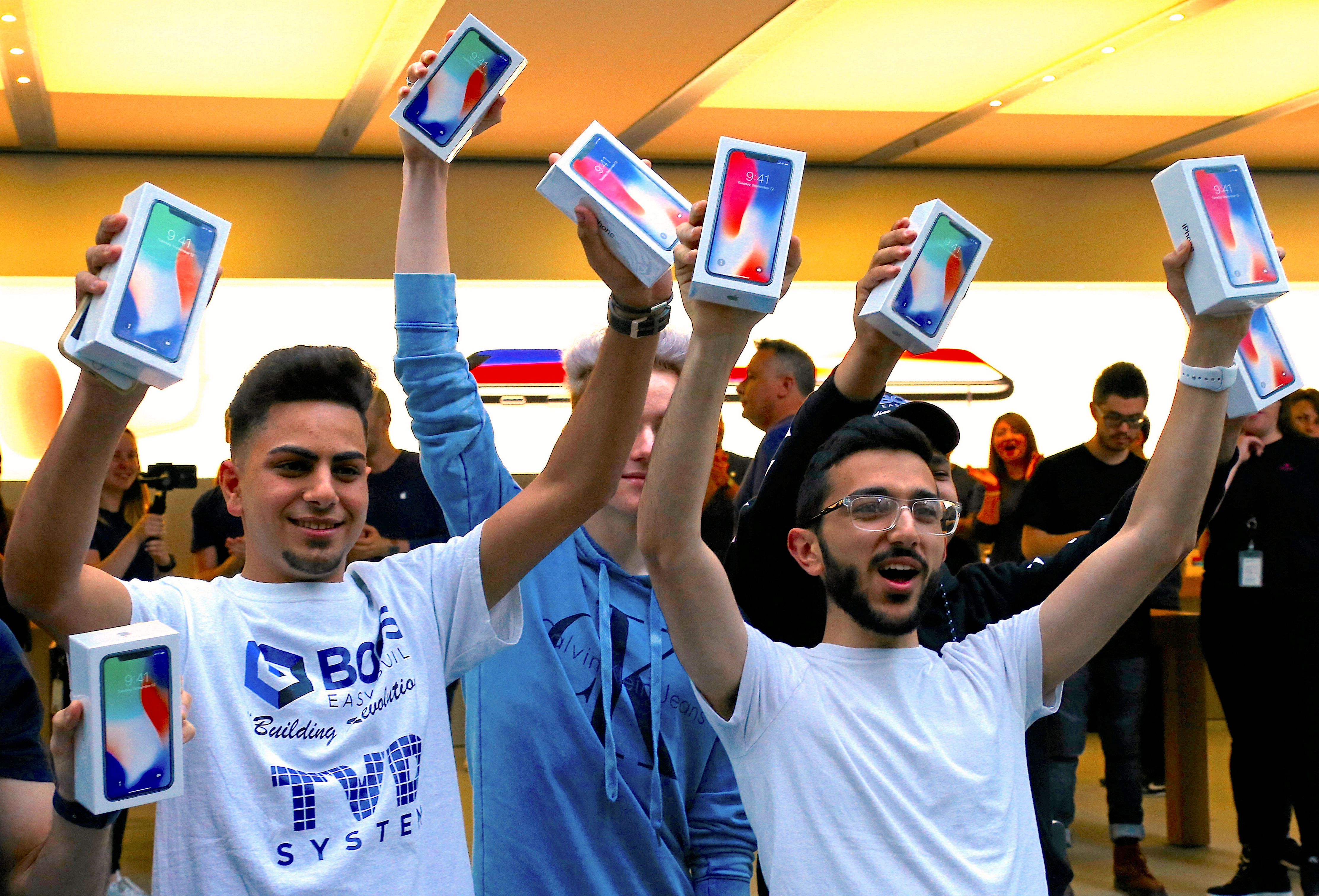 The first customers to buy the iPhone X react during global launch of the new Apple product in central Sydney