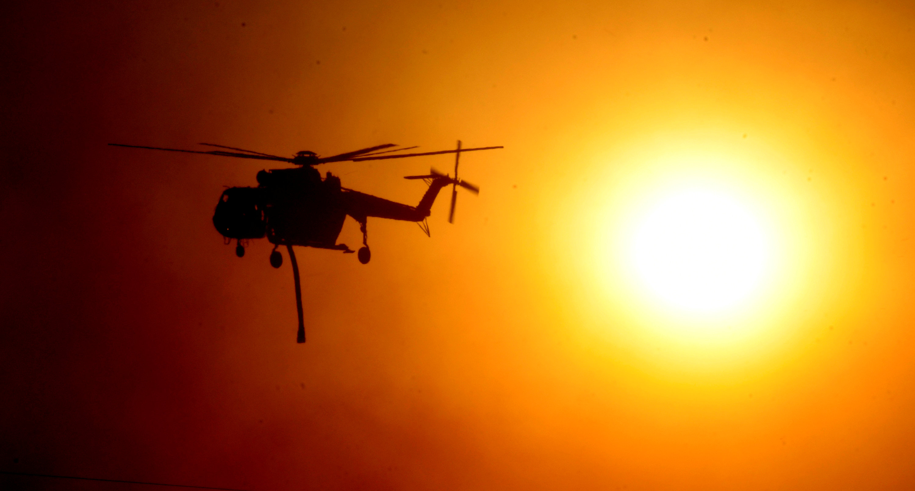 A firefighting helicopter passes by the smoke covered sun during an early-morning Creek Fire that broke out in the Kagel Canyon area in the San Fernando Valley north of Los Angeles in Sylmar