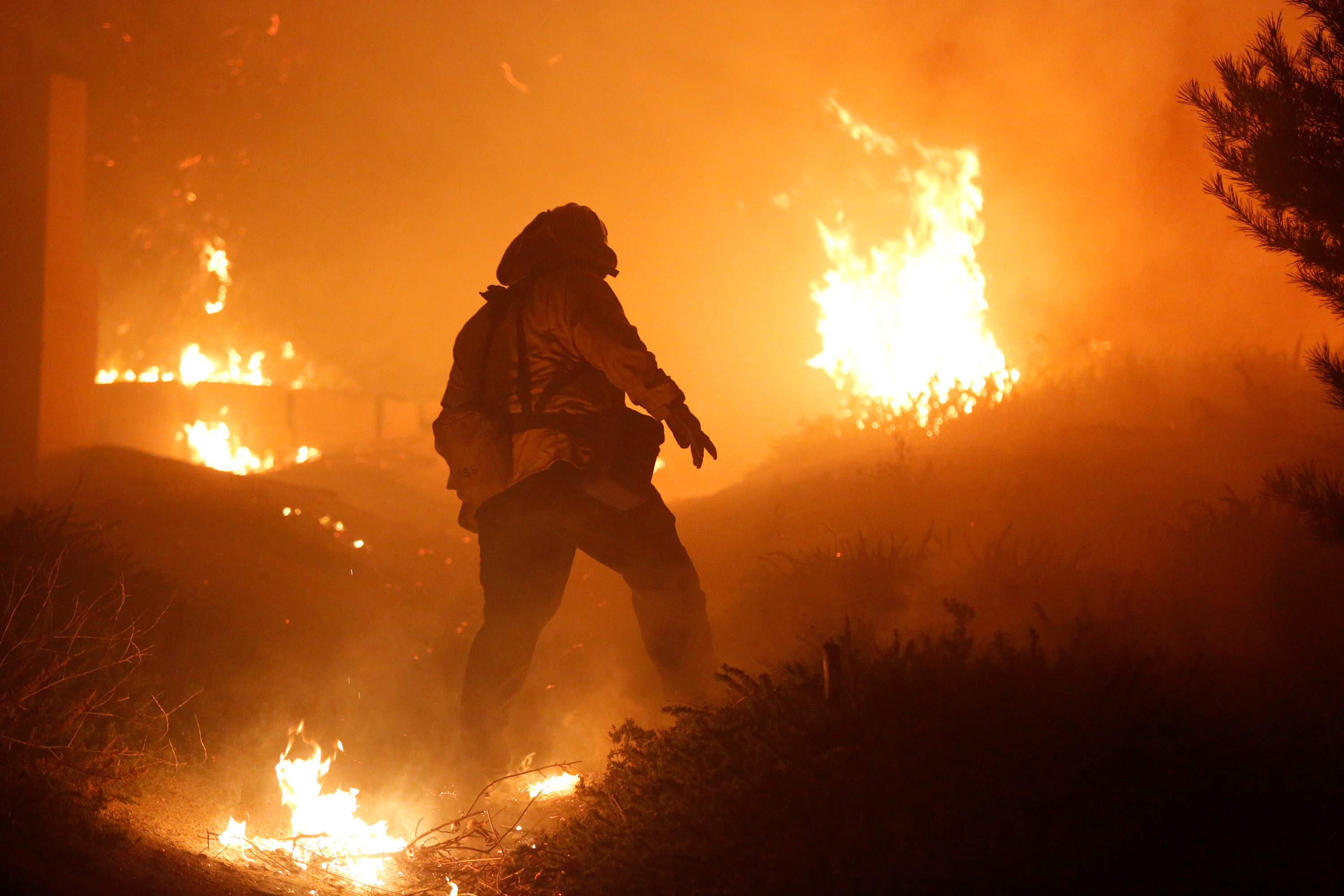 A firefighter stomps out small embers near a home threatened by the Creek Fire in Sylmar, California
