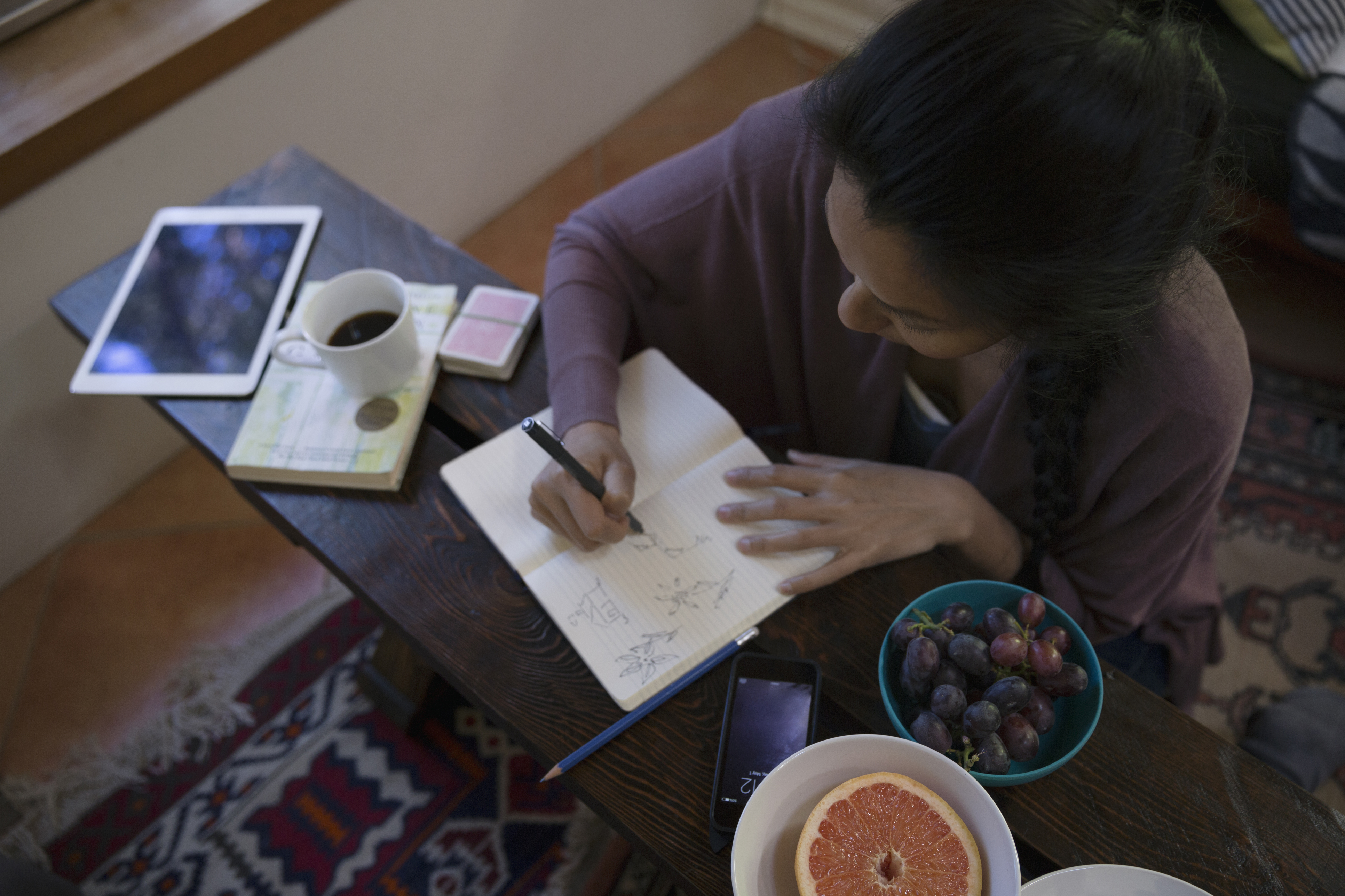 Woman sketching in journal in living room