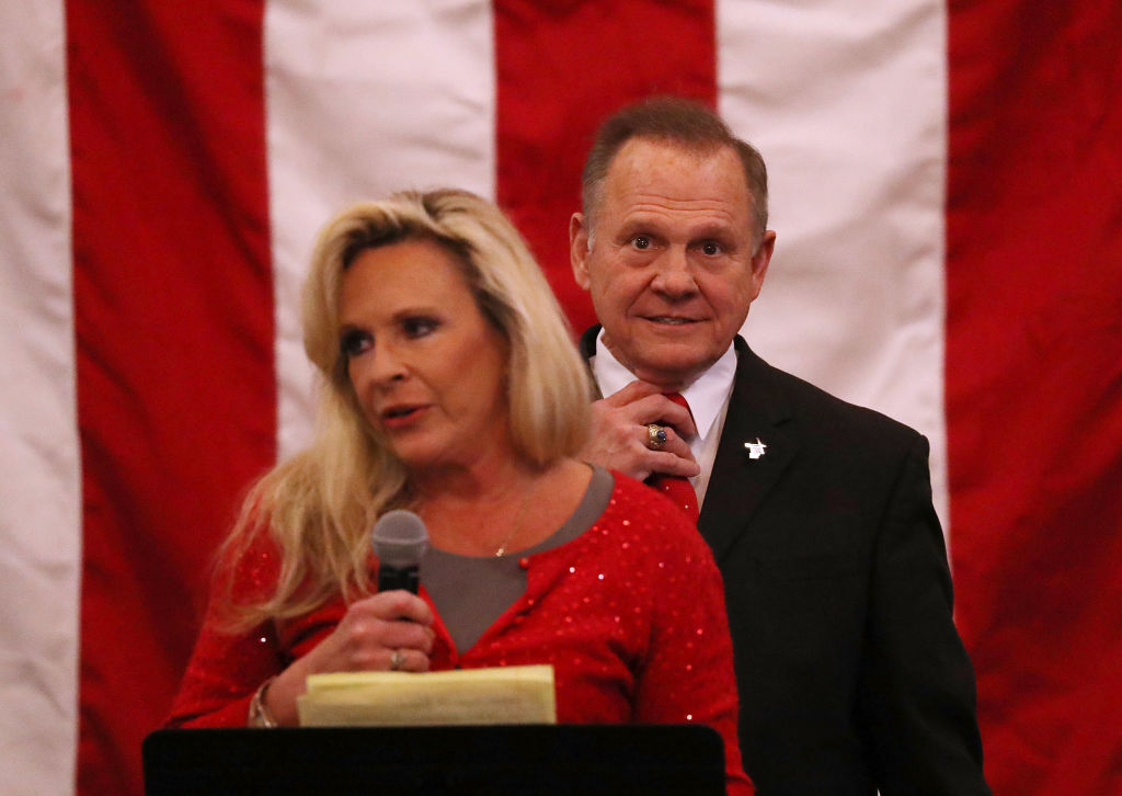 Roy Moore and wife Kayla appear on stage at campaign rally with American flag backdrop