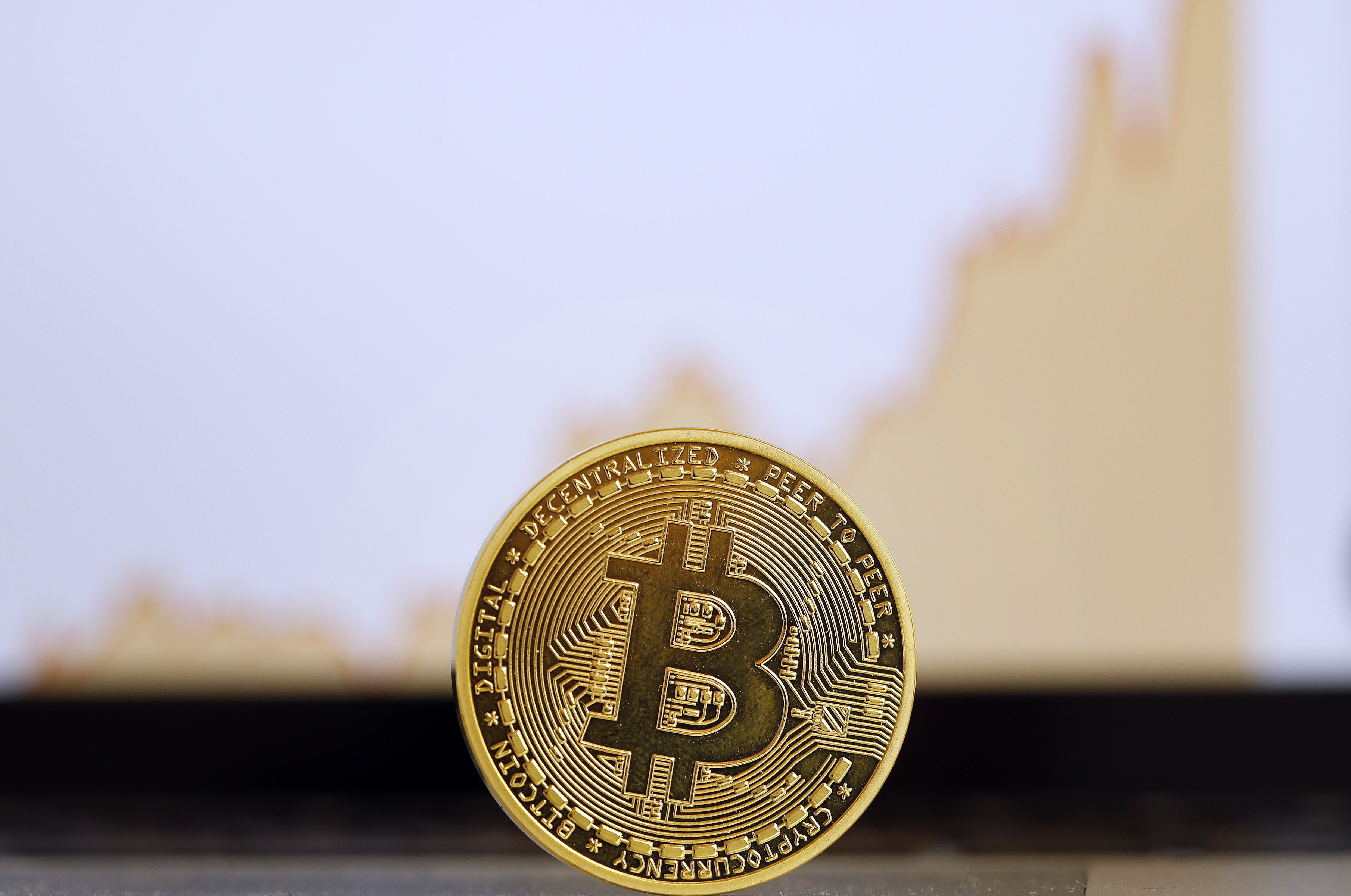 The digital cryptocurrency Bitcoin is visually displayed as a physical coin in front of a price chart is displayed on November 30, 2017 in Paris, France.