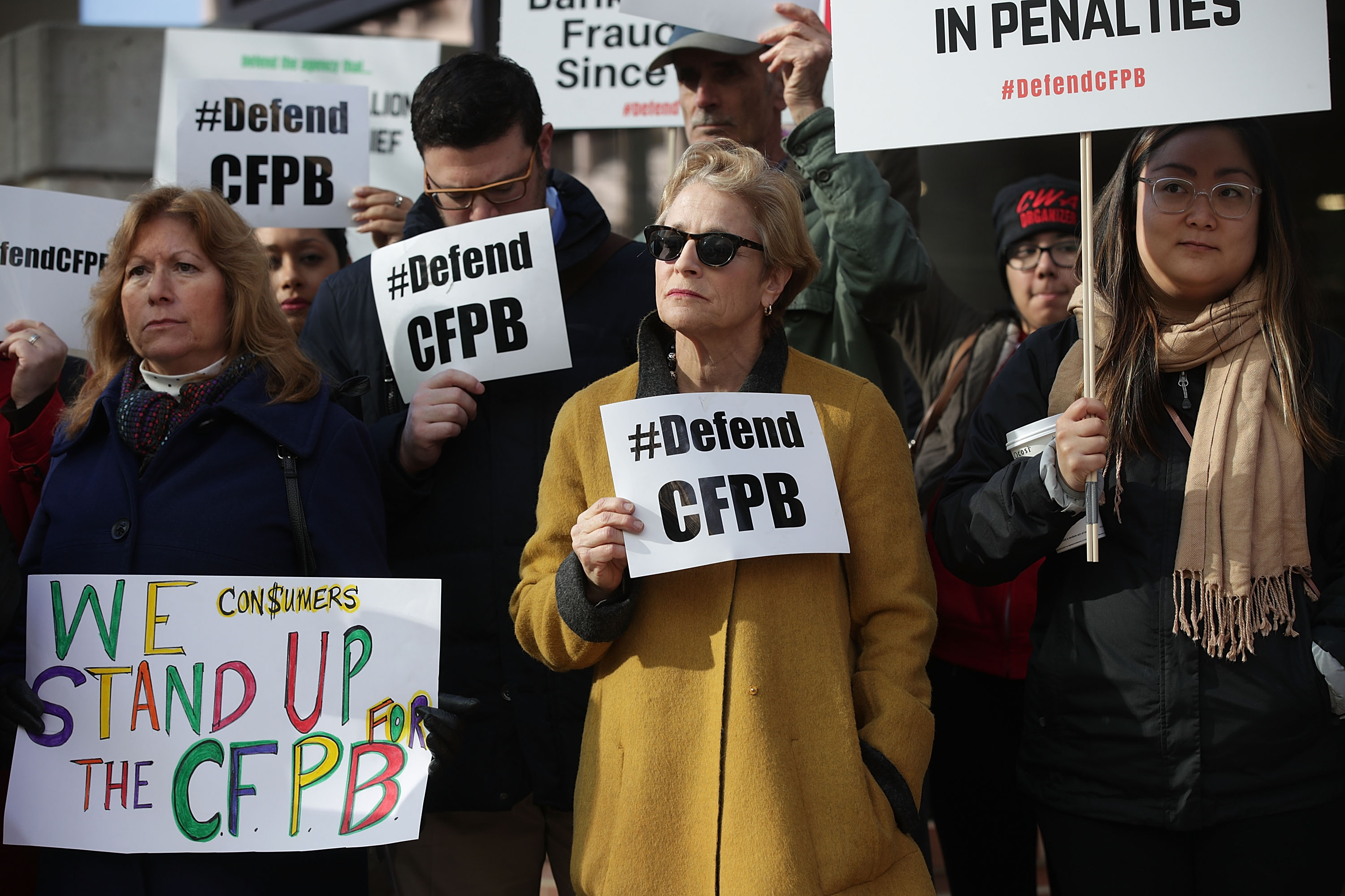 Supporters of the Consumer Financial Protection Bureau (CFPB) hold signs as they gather in front of the agency November 27, 2017 in Washington, DC.