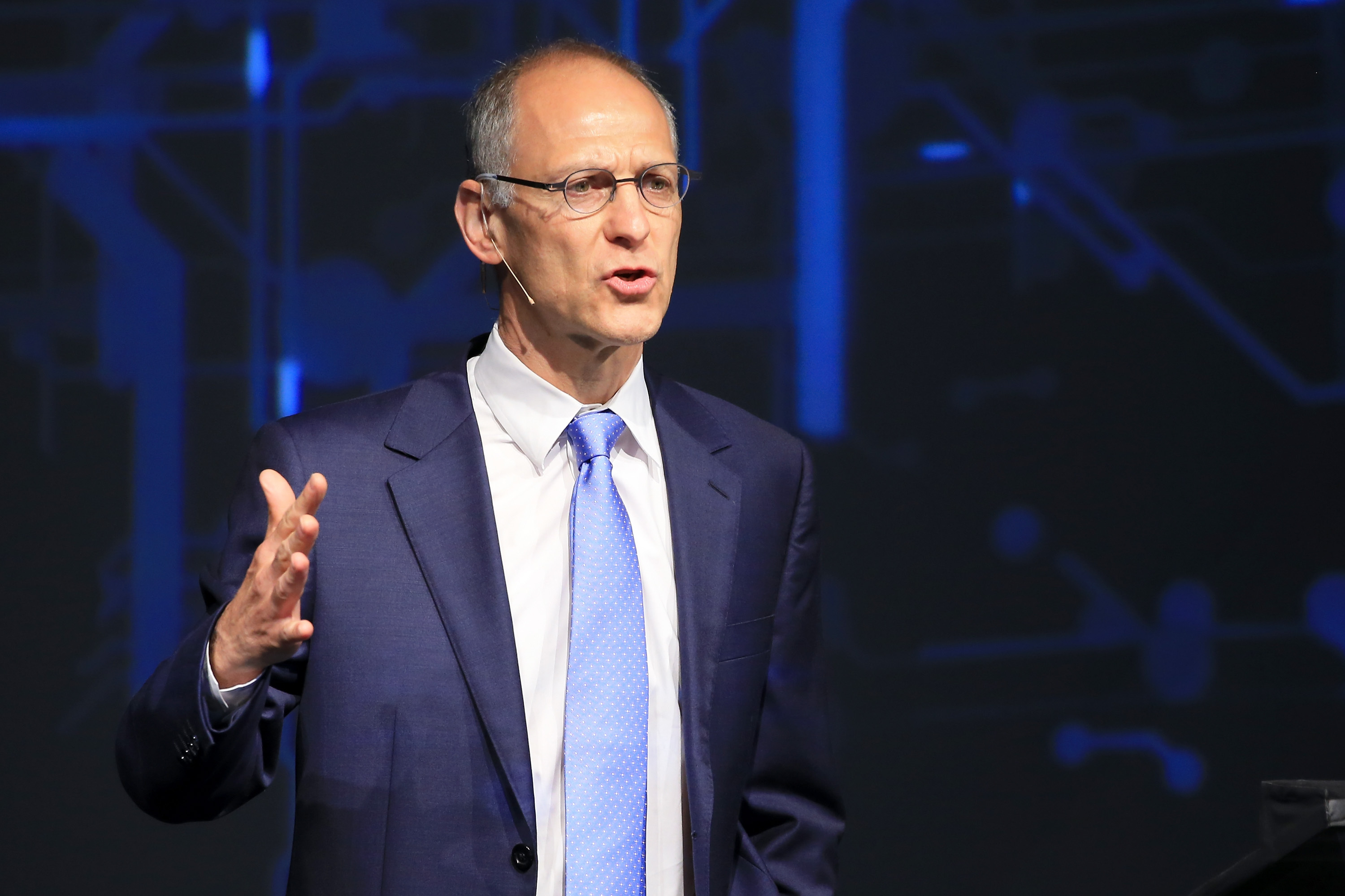 Ezekiel Emanuel speaking on stage at health conference and gesturing with his right hand in a forceful way