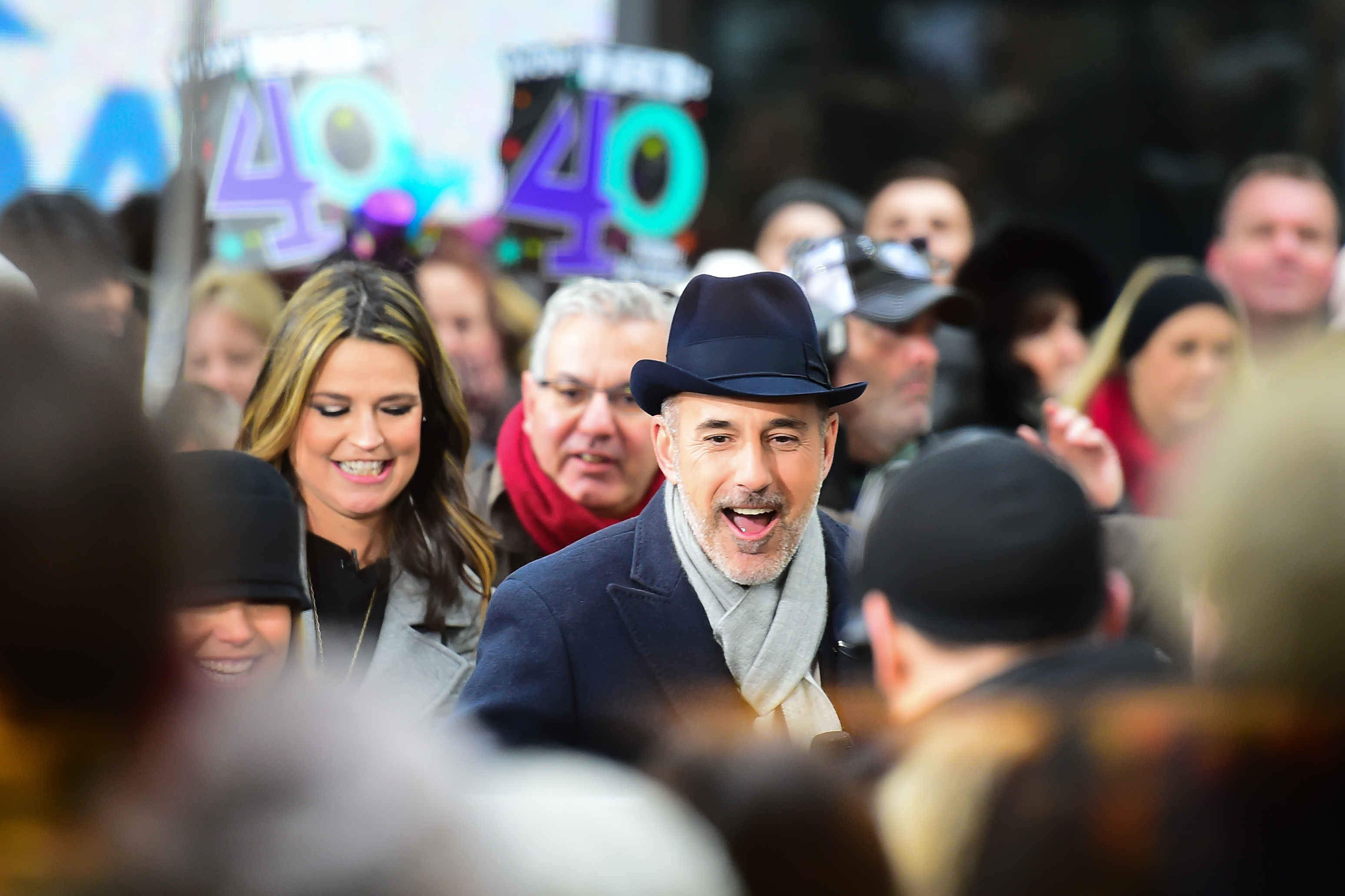 Matt Lauer smiling in a large crowd in New York City