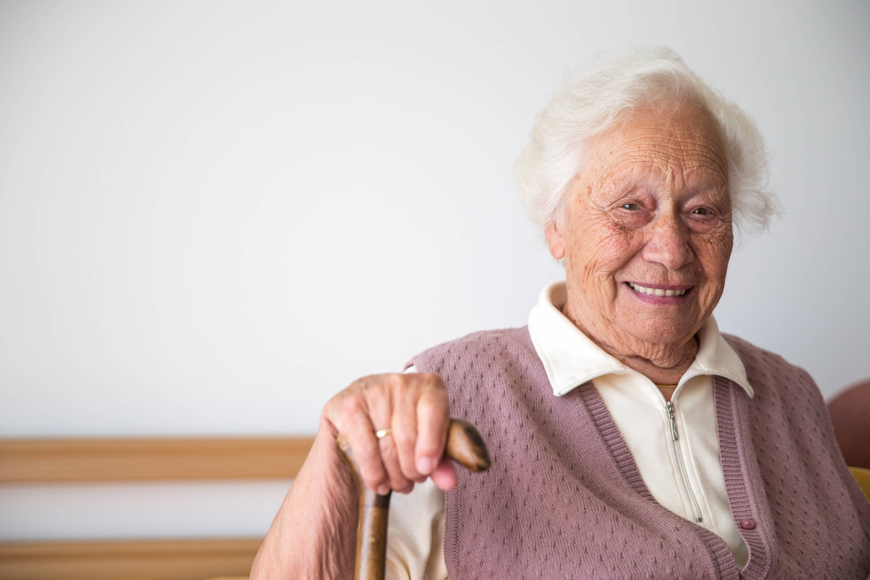 Portrait Of Smiling Senior Woman Relaxing In Her Bedroom At The Retirement Home