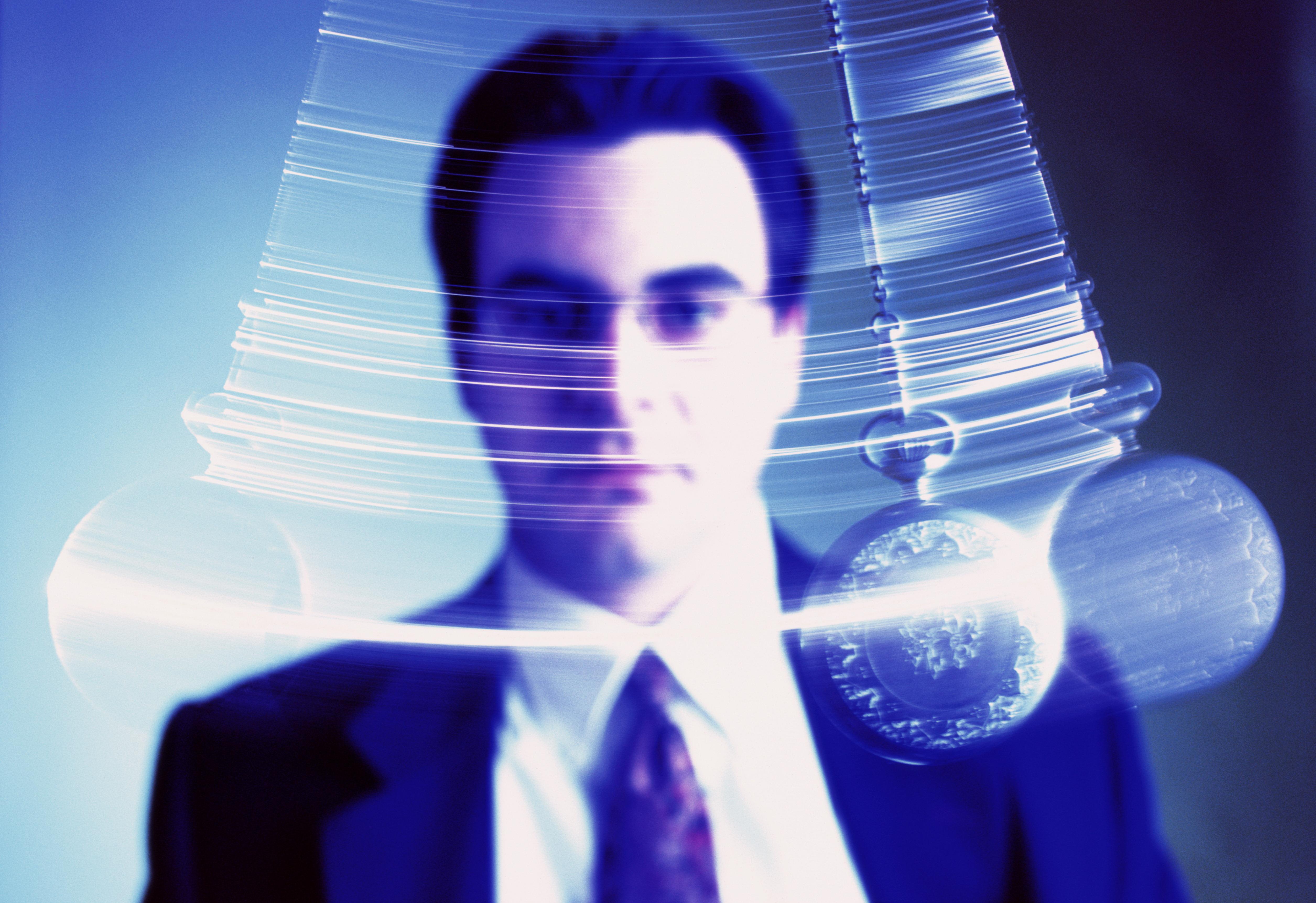 Businessman watching swinging pendulum (Digital Enhancement)
