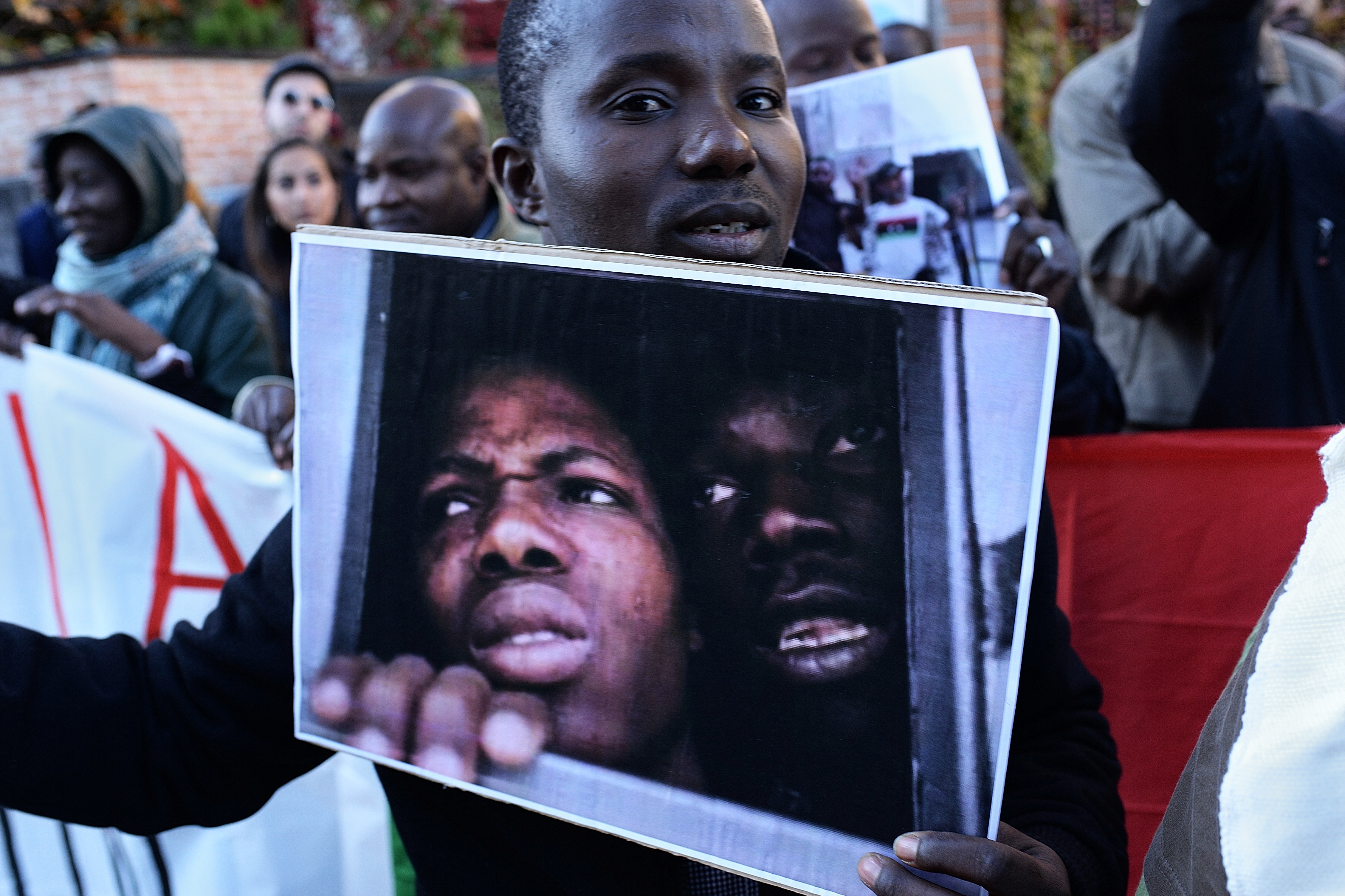 A man holds a photo during a protest against against slavery in Libya in front of the Libya embassy in Madrid on 26th November, 2017.
