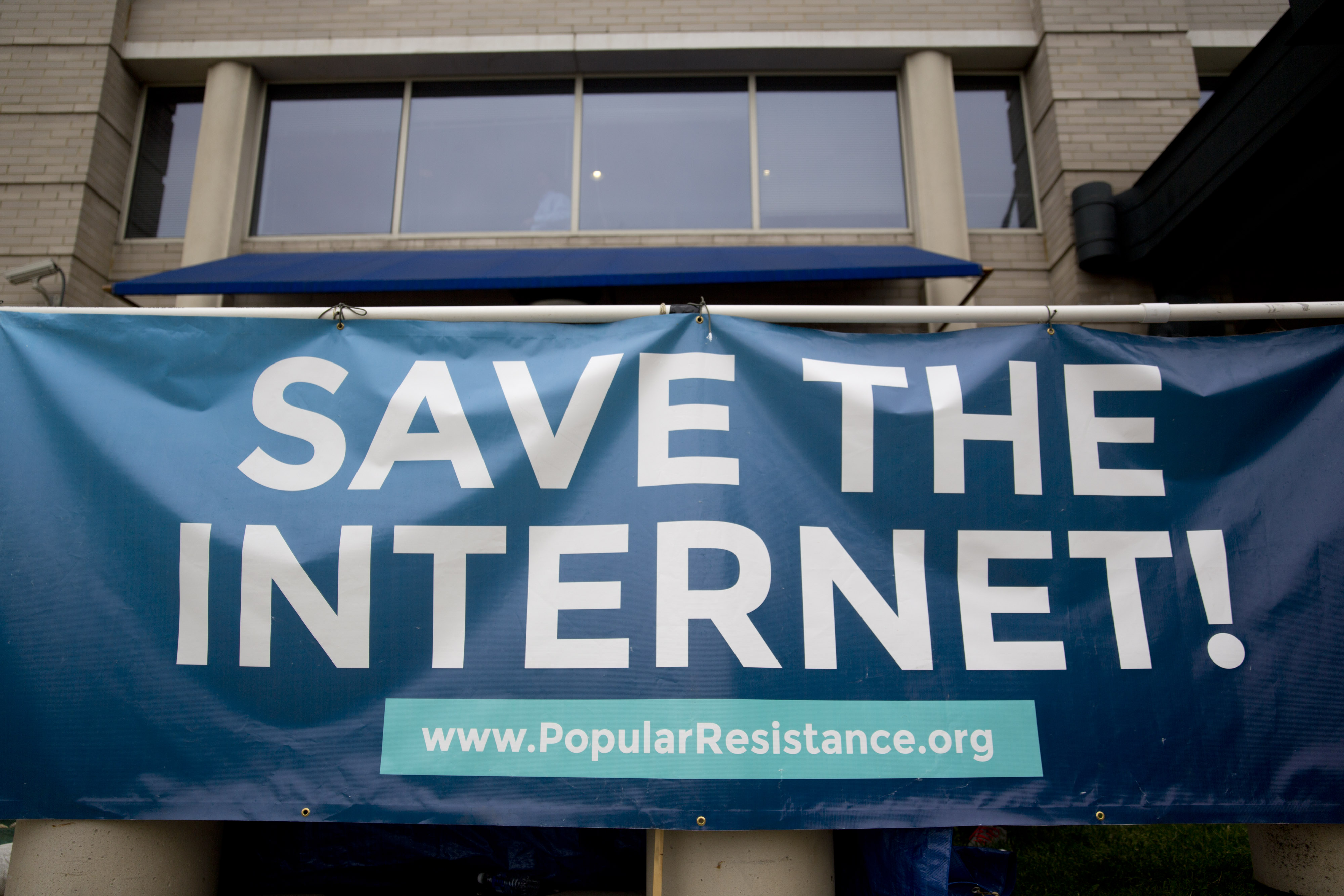 "A sign reading ""SAVE THE INTERNET!"" in support of net neutrality stands outside the Federal Communications Commission (FCC) headquarters in Washington, D.C., U.S., on Wednesday, May 14, 2014."