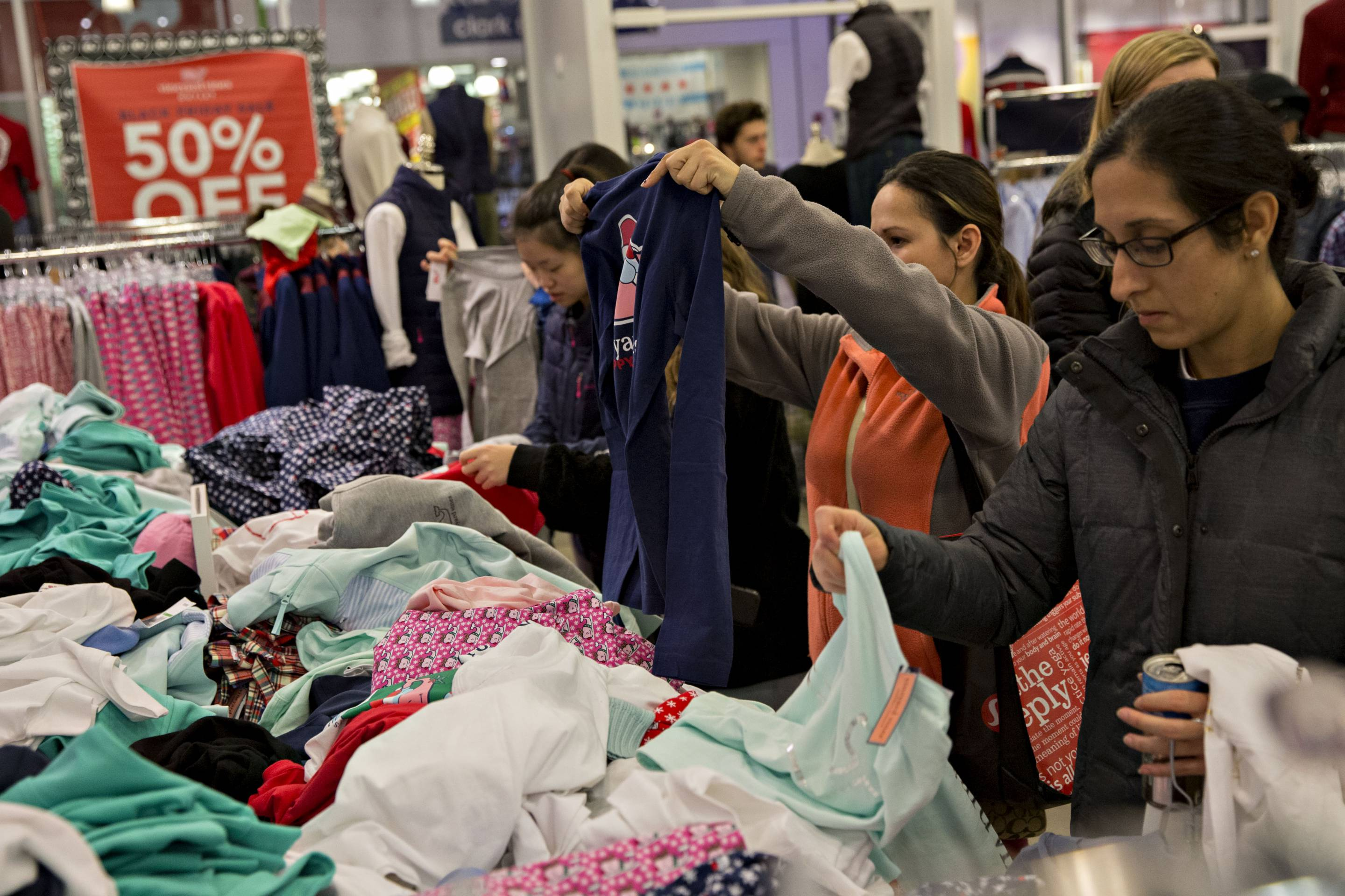 Shoppers look at clothes in a Vineyard Vines store in Chicago, Illinois, U.S., on Thursday, Nov. 23, 2017.