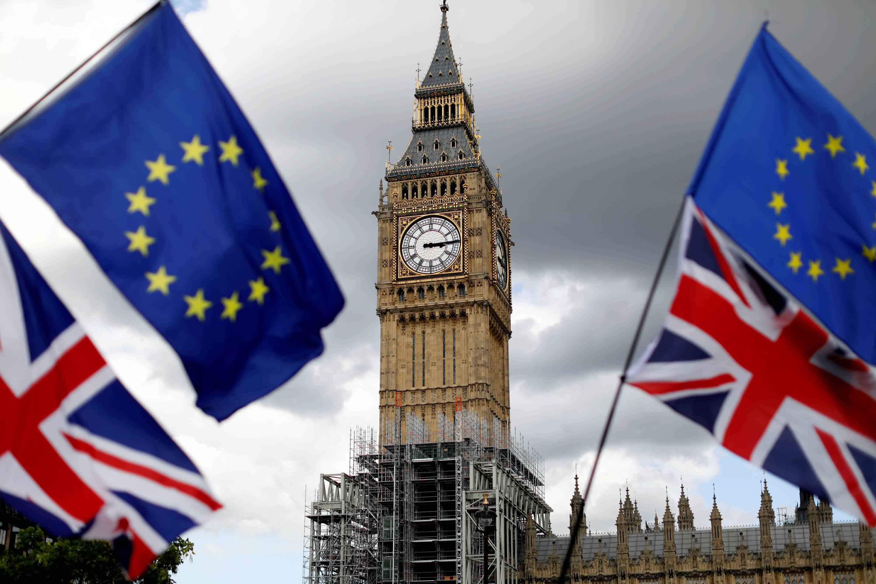 FILE PHOTO: Union Flags and European Union flags fly near the Elizabeth Tower, housing the Big Ben bell, during the anti-Brexit 'People's March for Europe', in Parliament Square in central London