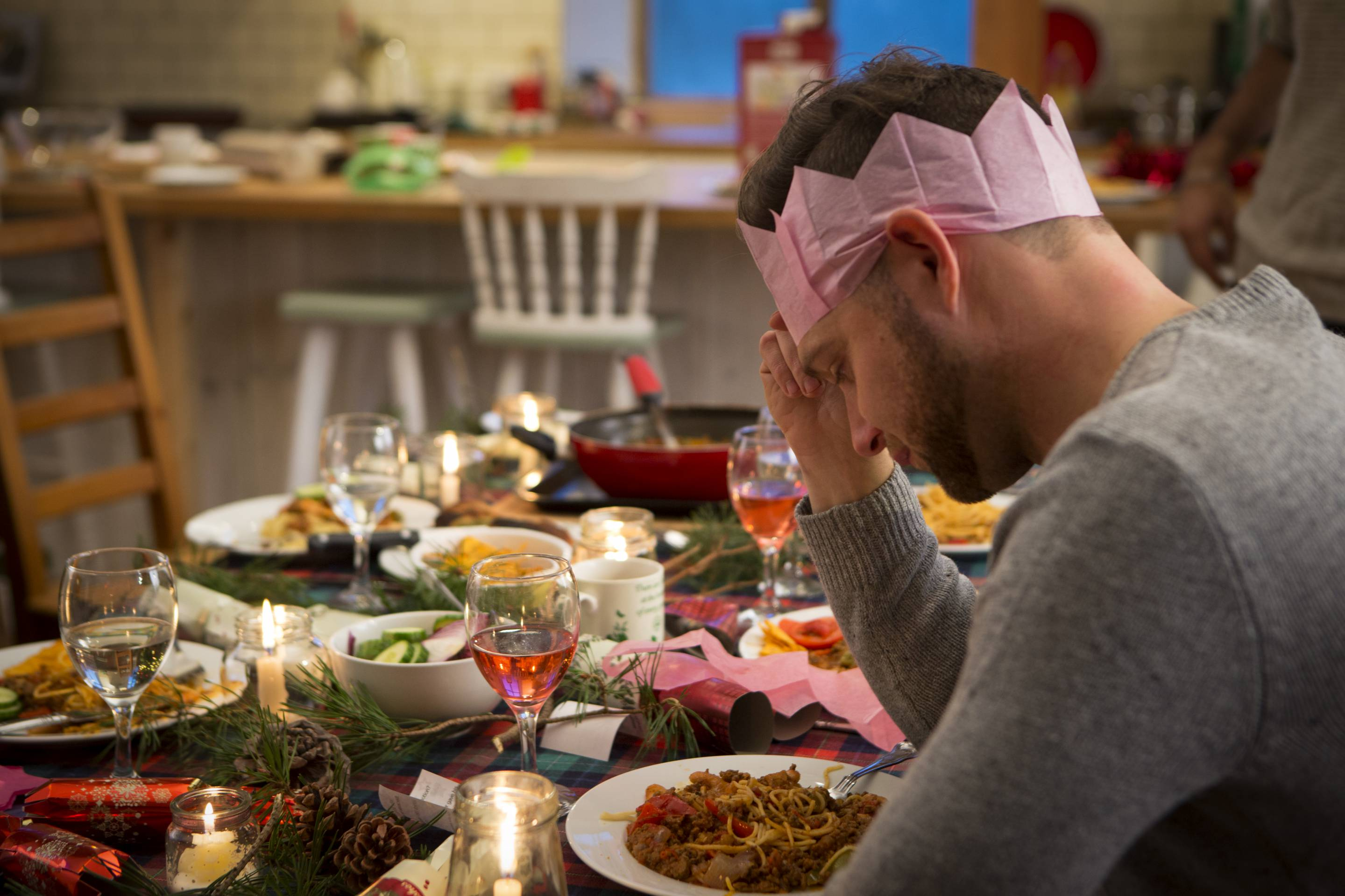 A man sits at a dinner table at Christmas looking sad as his head is lowered and resting on his hand. He sits with a pink hat on, alone with a plate of food in front of him.