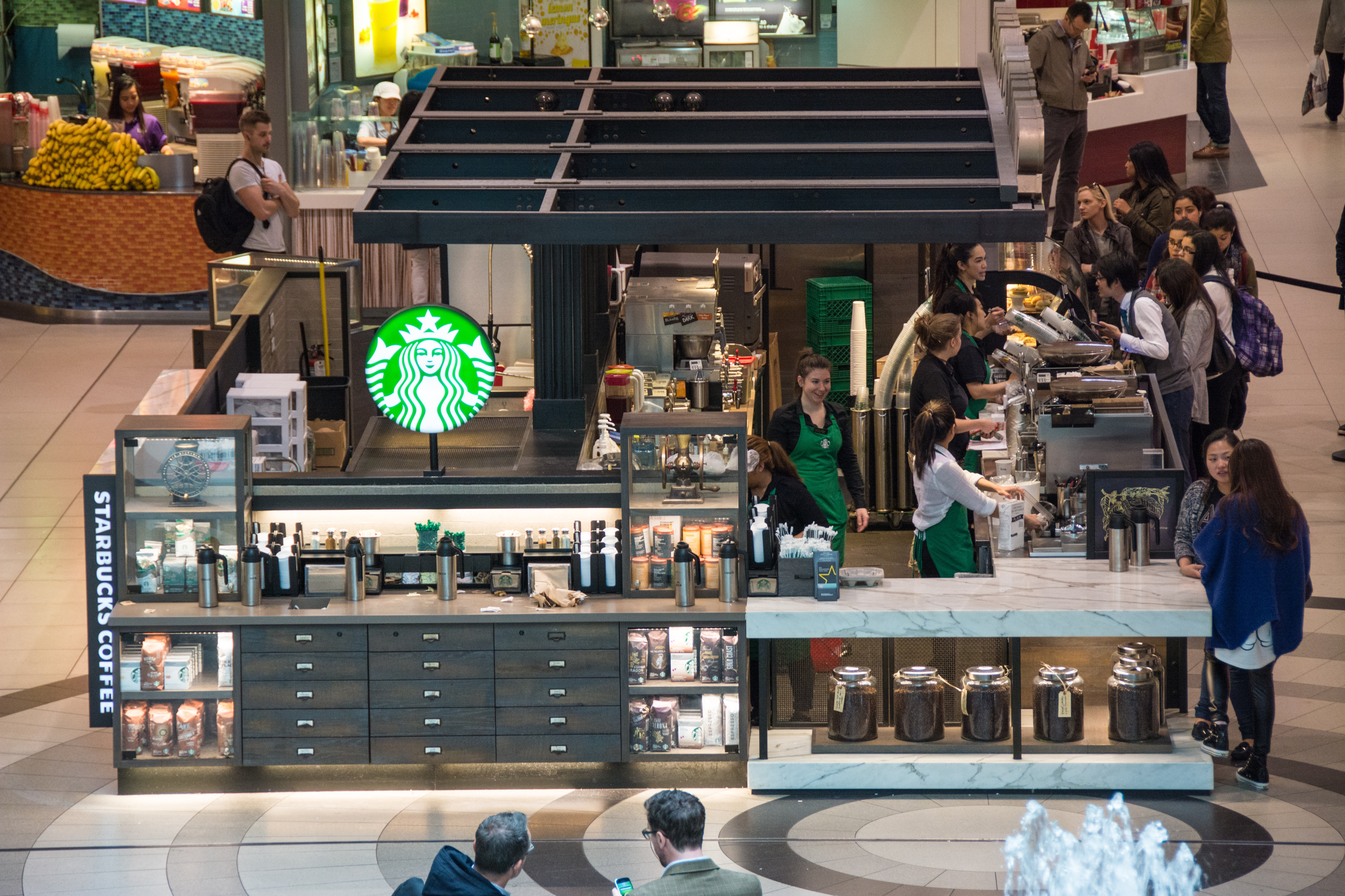 Starbucks in a shopping mall.  Four baristas surround a