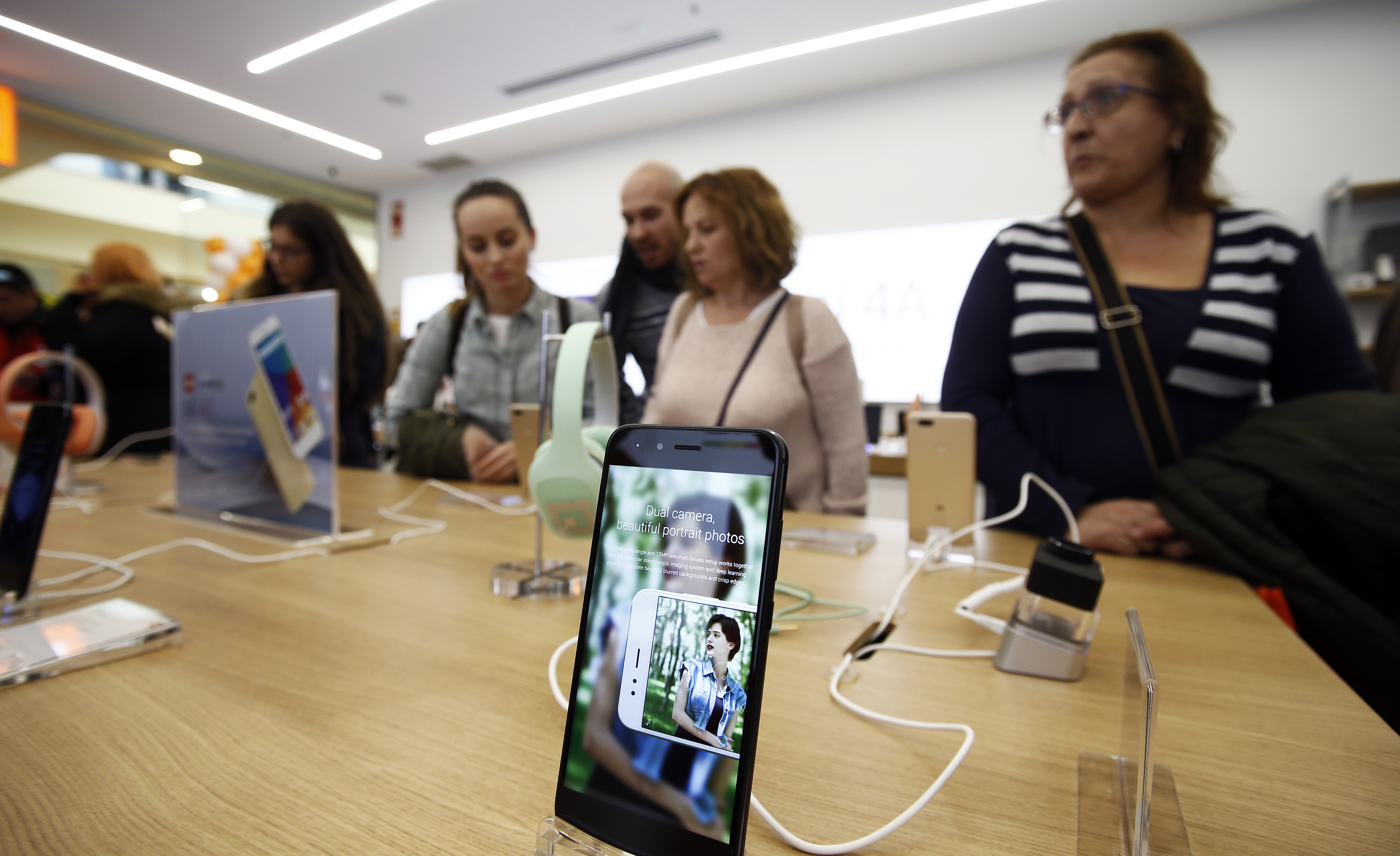 Customers stand at a table behind a smartphone display at Xiaomi's first store in Spain.