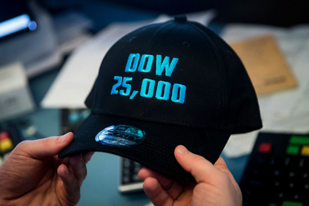 A trader holds a baseball hat that says 'Dow 25,000'