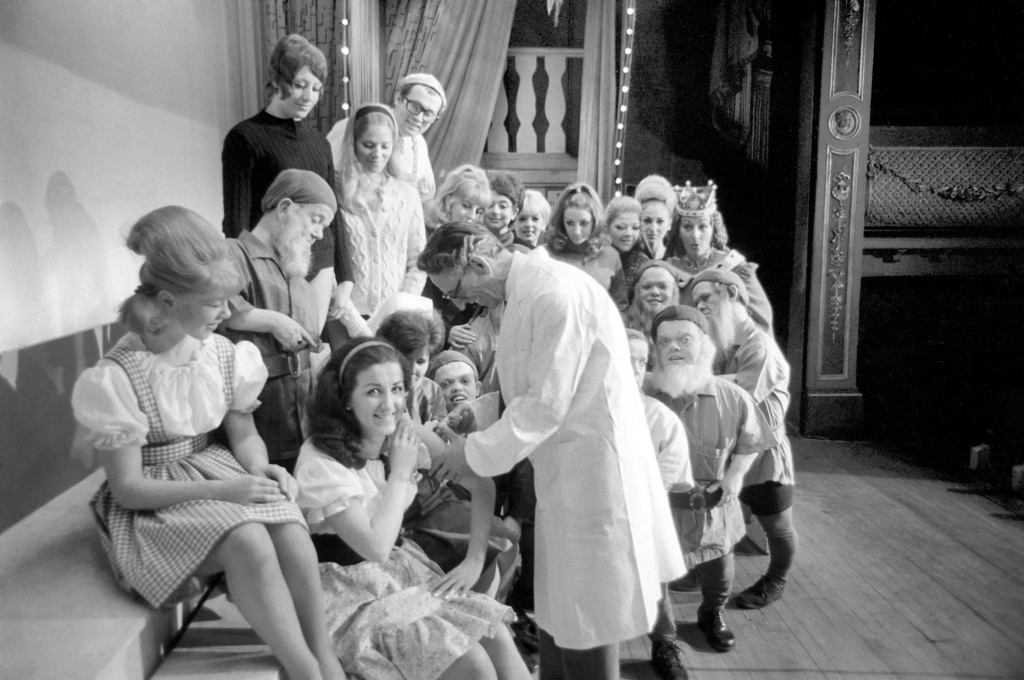A doctor with his syringe makes ready to give anti-flu vaccine to Margaret Ayre, who plays Snow White and the rest of th