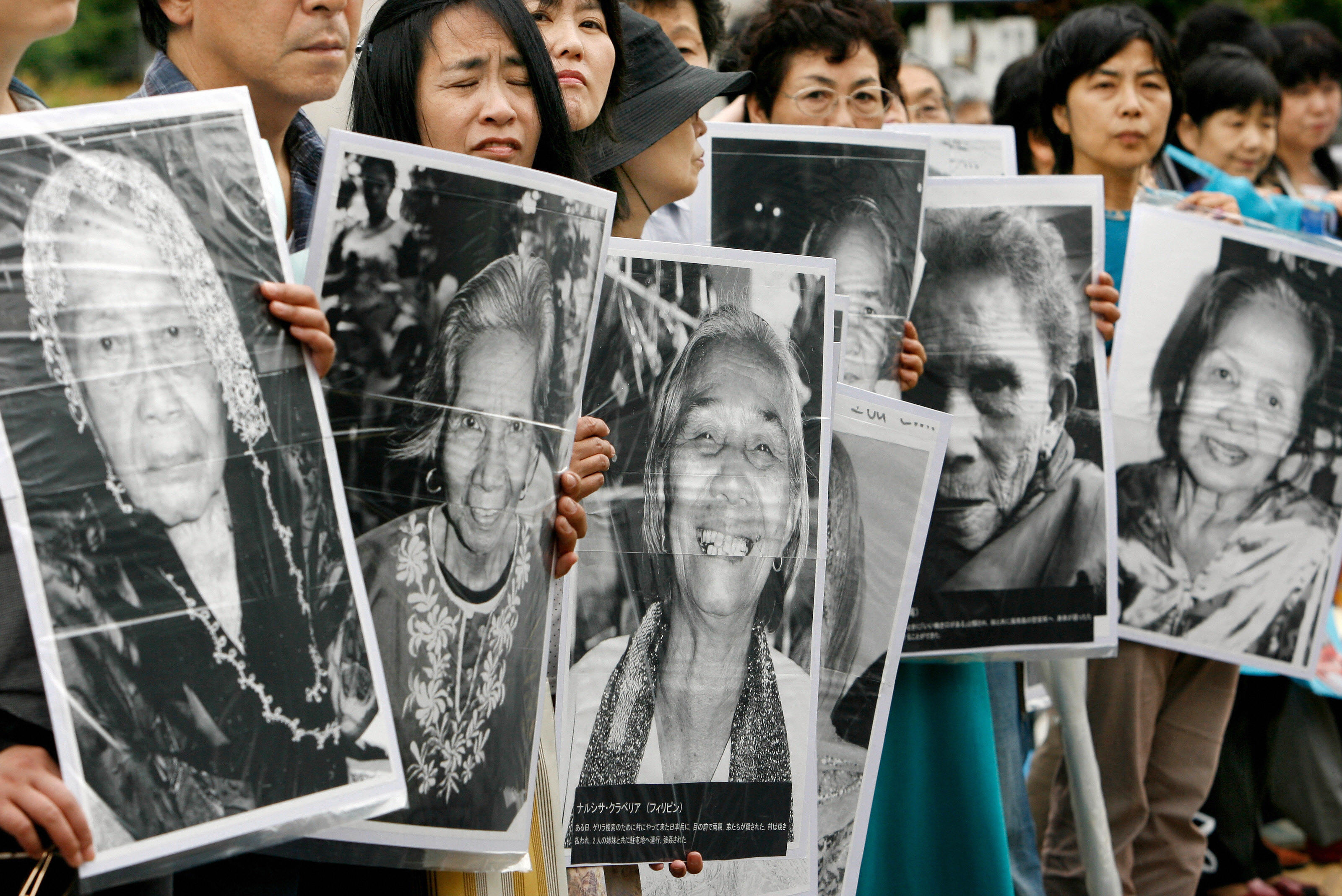 Japanese women hold portraits of Chinese