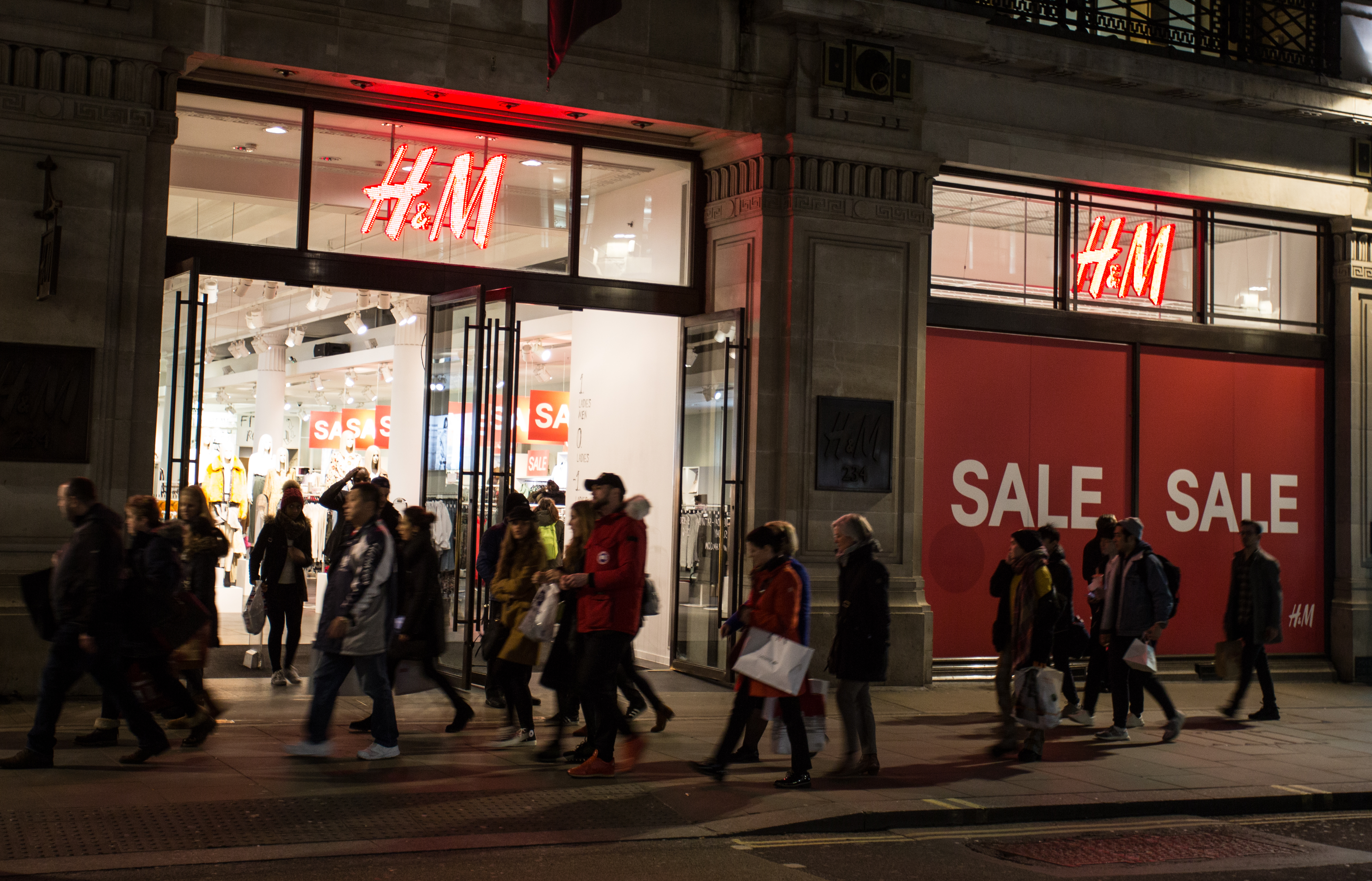 People walk past a 'sale' advertisement from an H&M store on