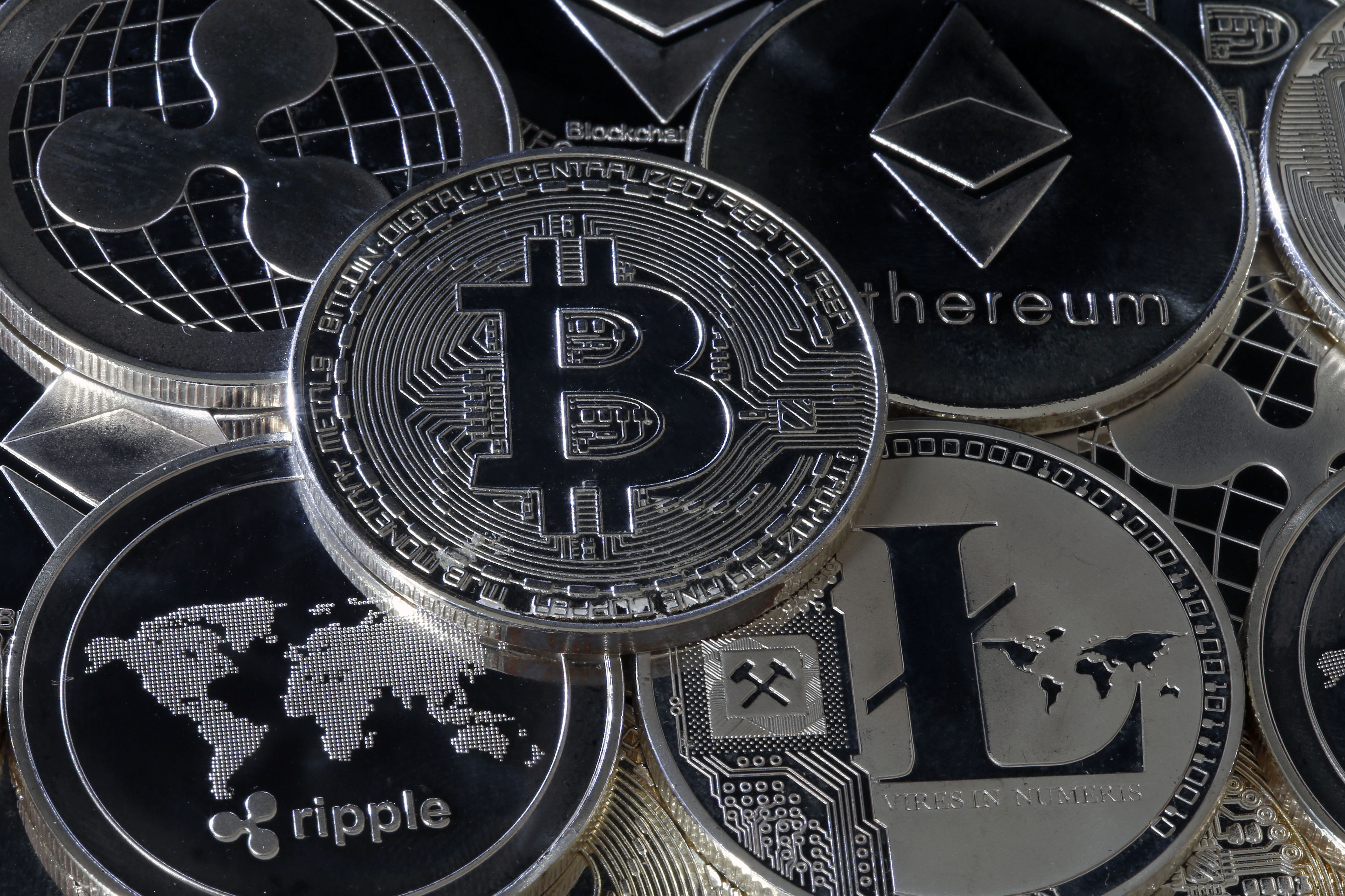 Digital cryptocurrencies Ripple, Bitcoin, Ethereum, and Litecoin represented as silver coins.