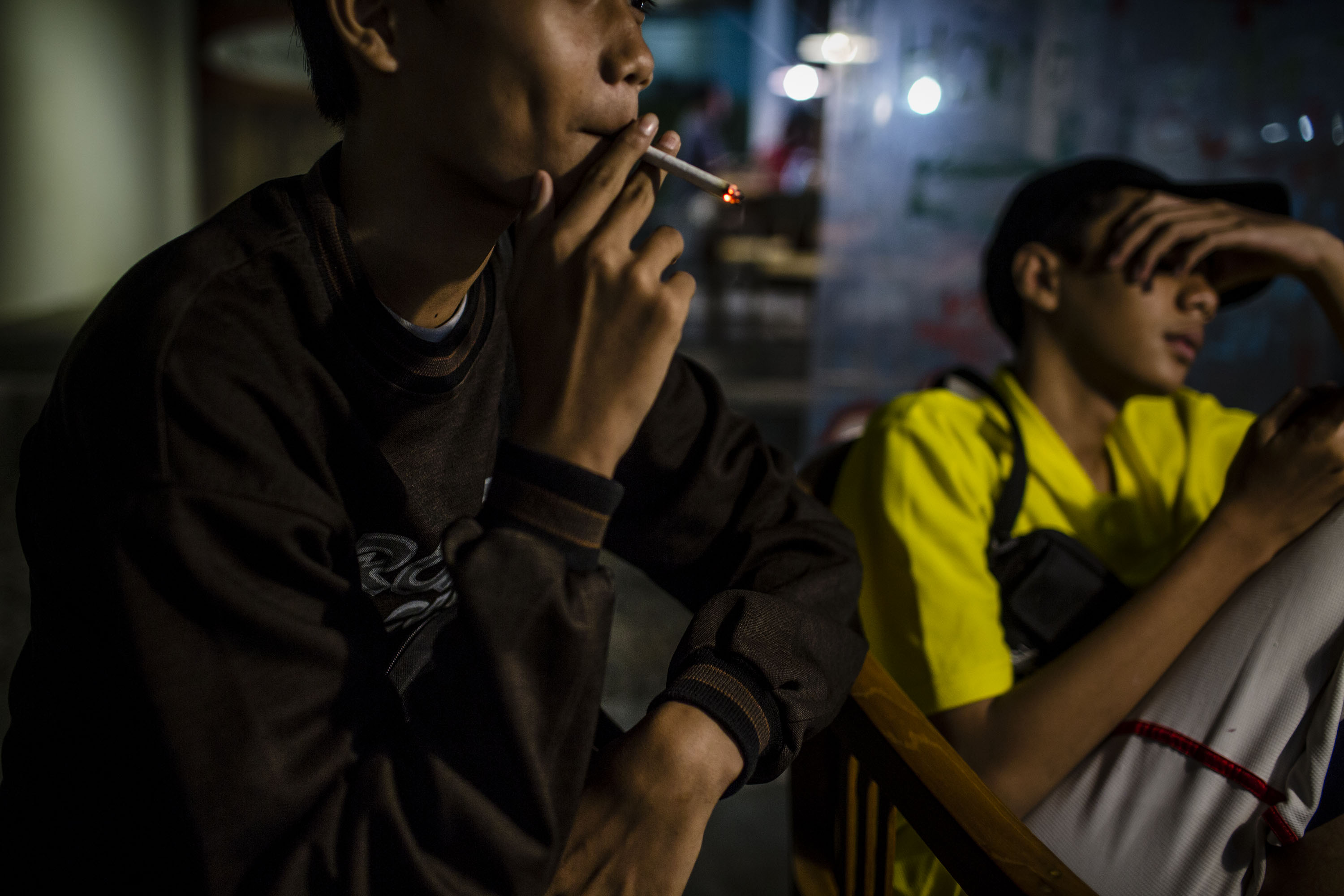 A boy smokes at a coffee shop at night with his friends on March 7, 2017 in Yogyakarta, Indonesia.