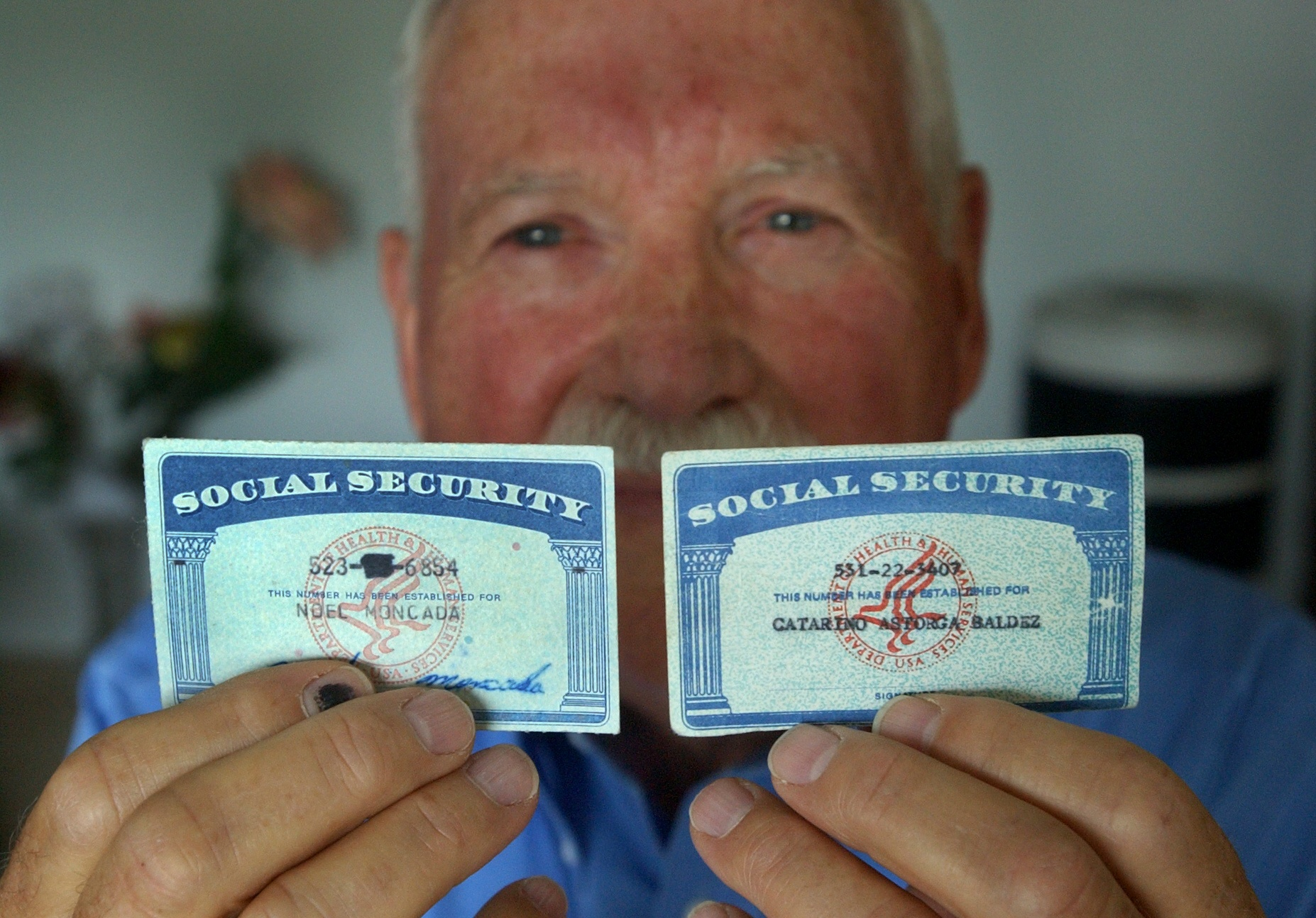 A man holds up two social security cards, one real and one fake.