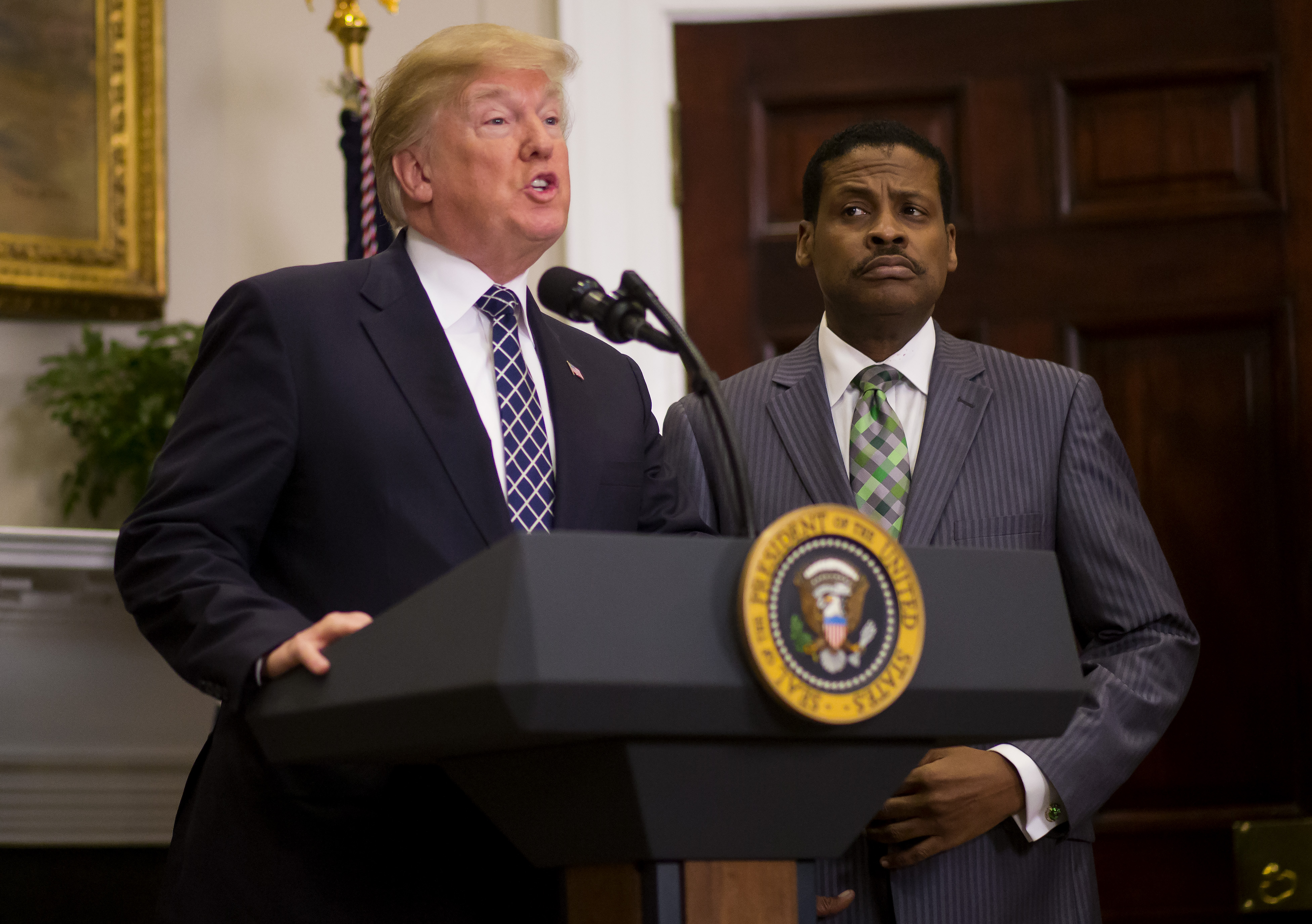 U.S. President Donald Trump, left, speaks while Martin Luther King Jr.'s nephew Isaac Newton Farris Jr. listens before the signing of a proclamation in the Roosevelt Room of the White House in Washington, D.C., U.S., on Friday, Jan. 12, 2018.