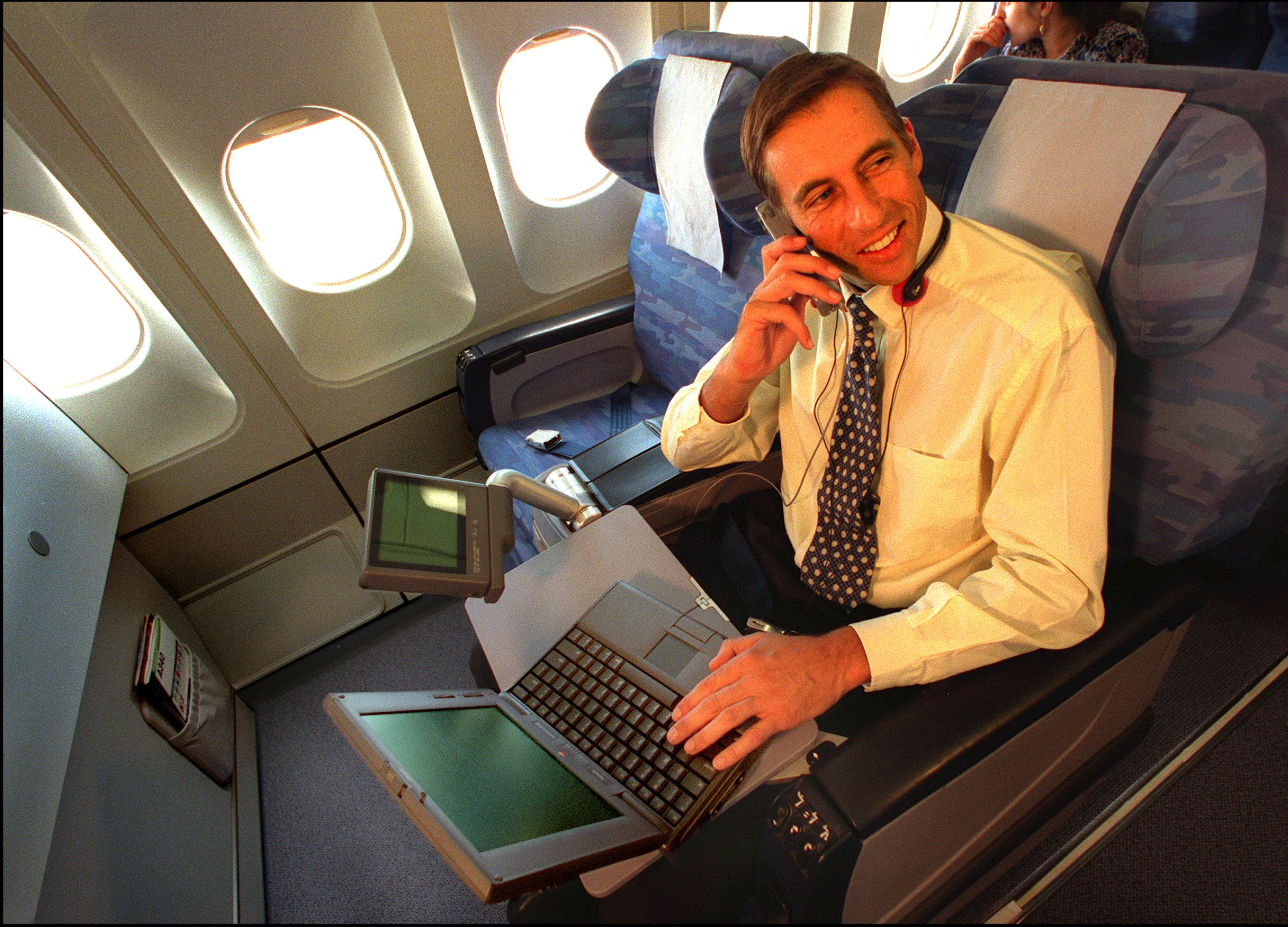 Airline passenger talks on block cell phones with bulky laptop