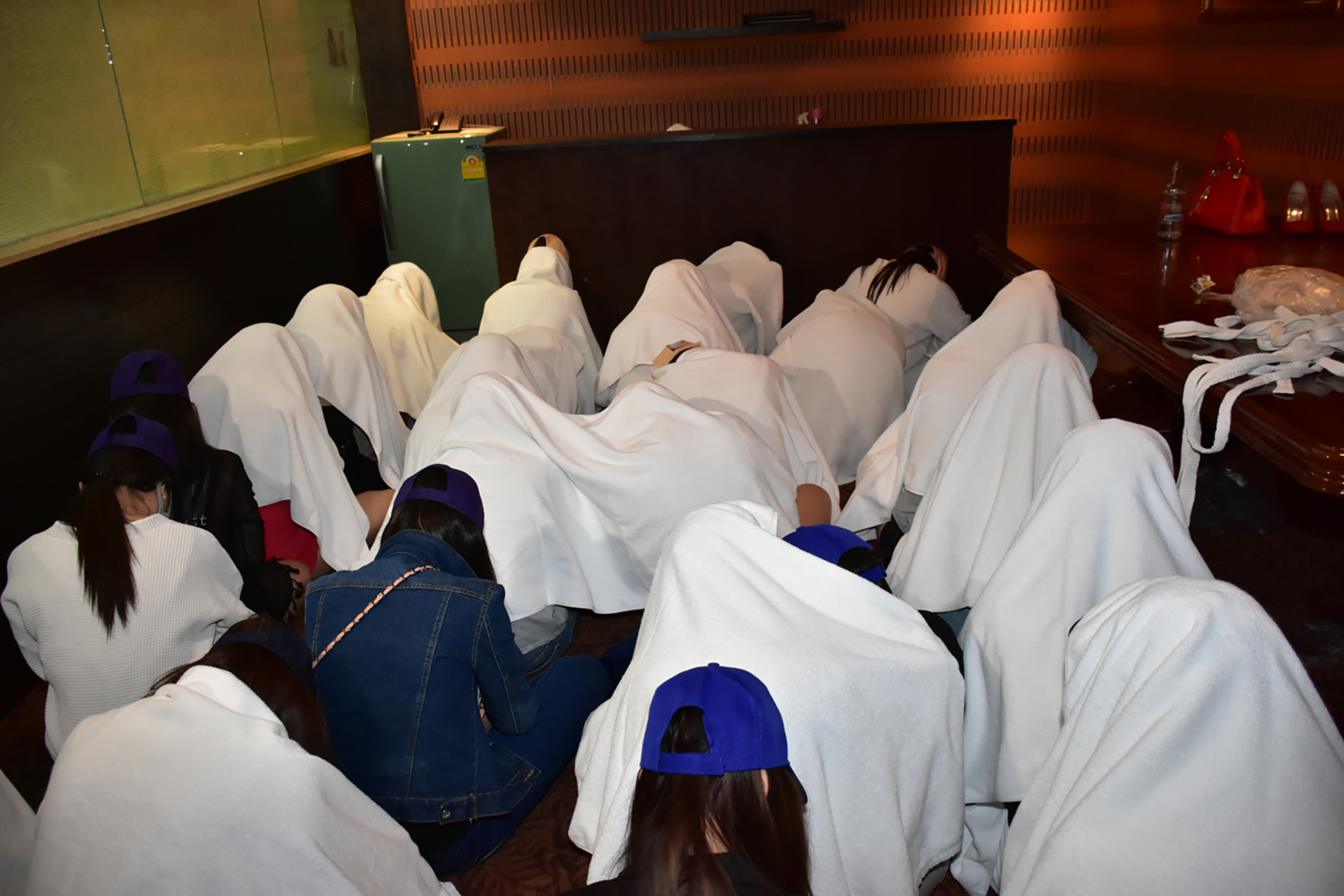Female workers detained at a massage parlor in Thailand after police raided the premises on suspicions of underage trafficking and prostitution.