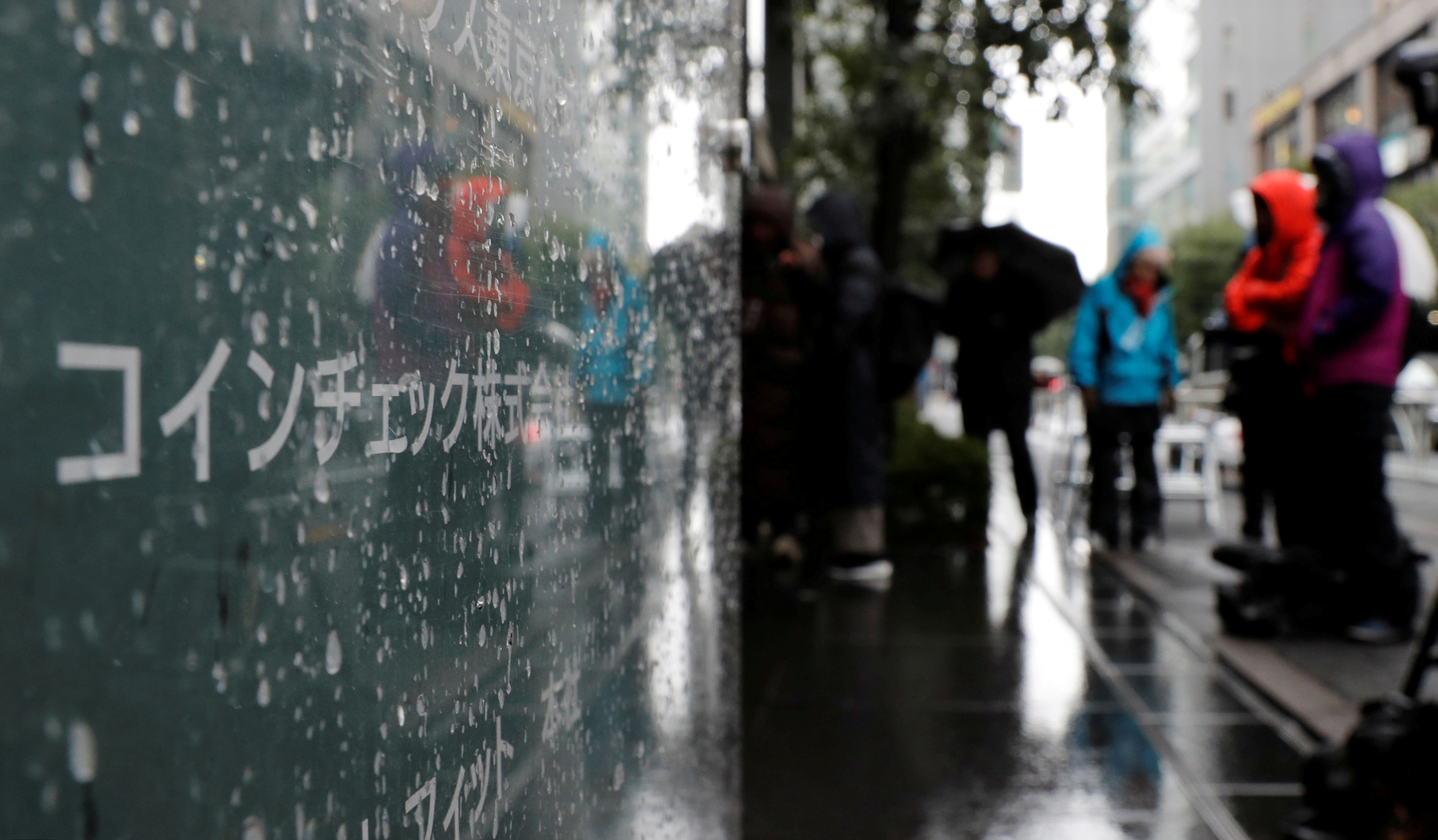 FILE PHOTO: Journalists are seen next to Cryptocurrency exchange Coincheck's signboard while Japan's financial regulator conducts a spot inspection on Coincheck, in Tokyo