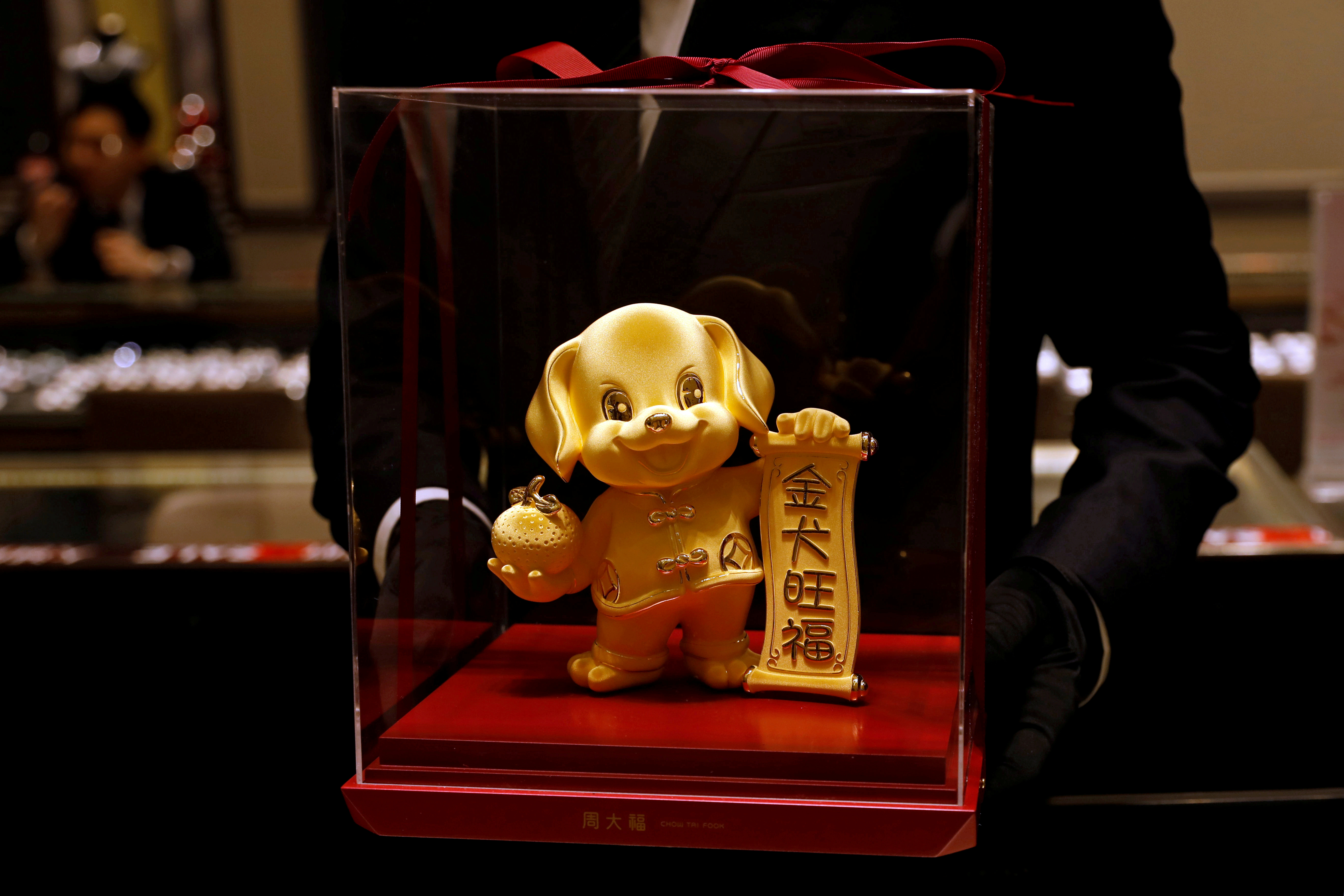 FILE PHOTO: A staff poses with a dog-shaped gold figurine, at Chow Tai Fook Jewellery store ahead of the Lunar Year of the Dog in Hong Kong