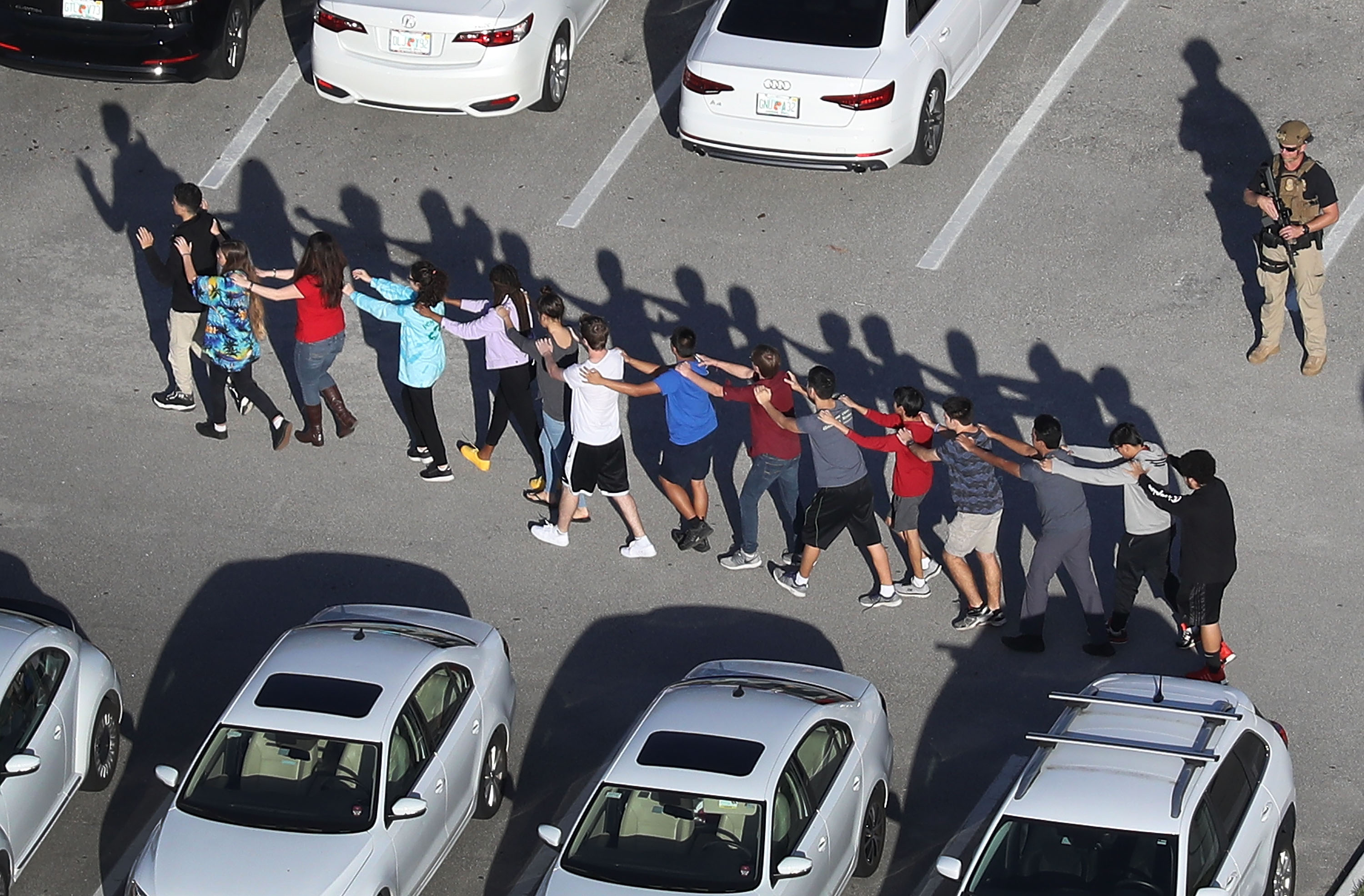 Students walk out of Marjory Stoneman Douglas High School in Parkland Florida after a shooting there. America is now debating arming teachers and gun control.