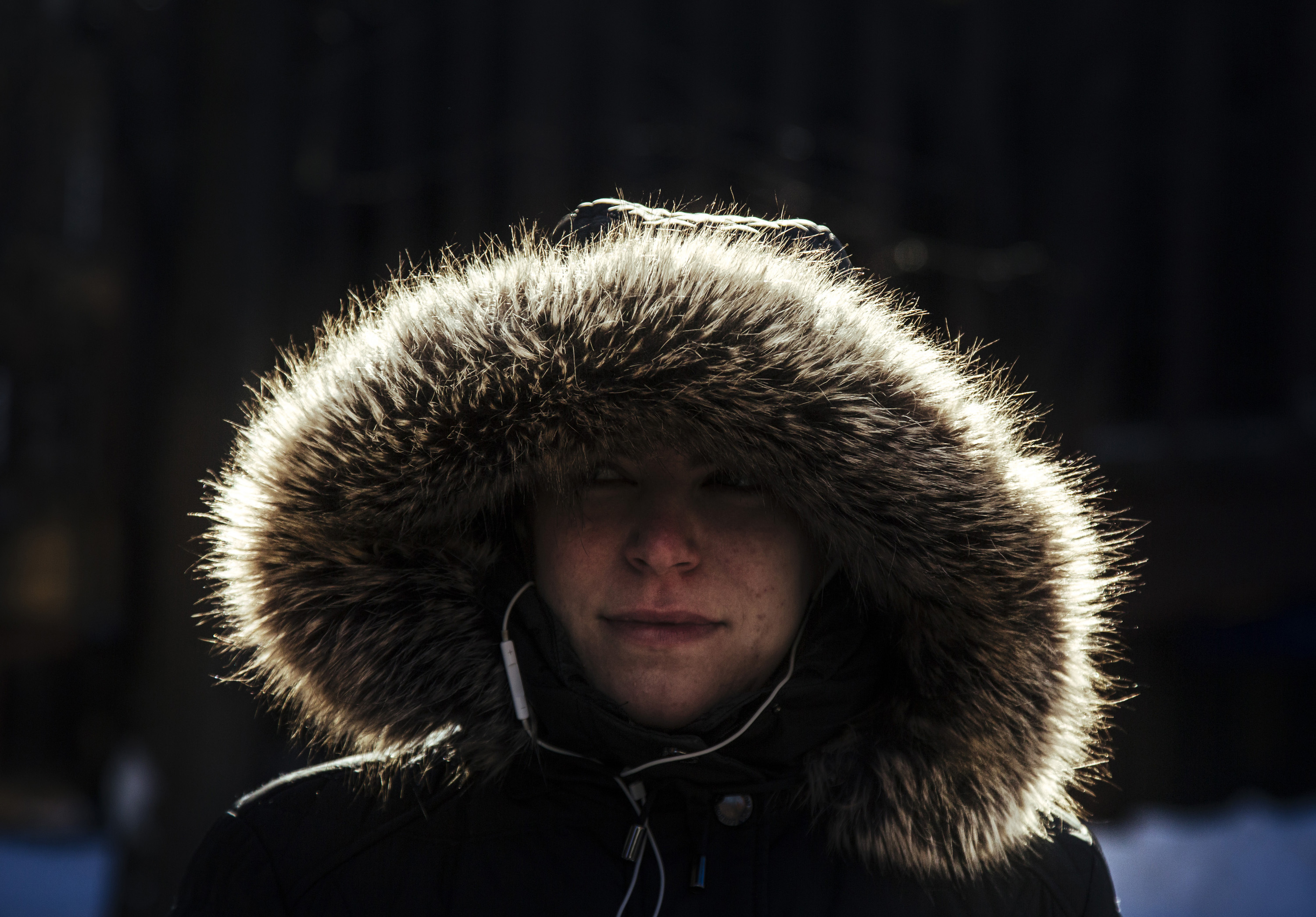 Woman wears hooded coat with fur trim in cold weather