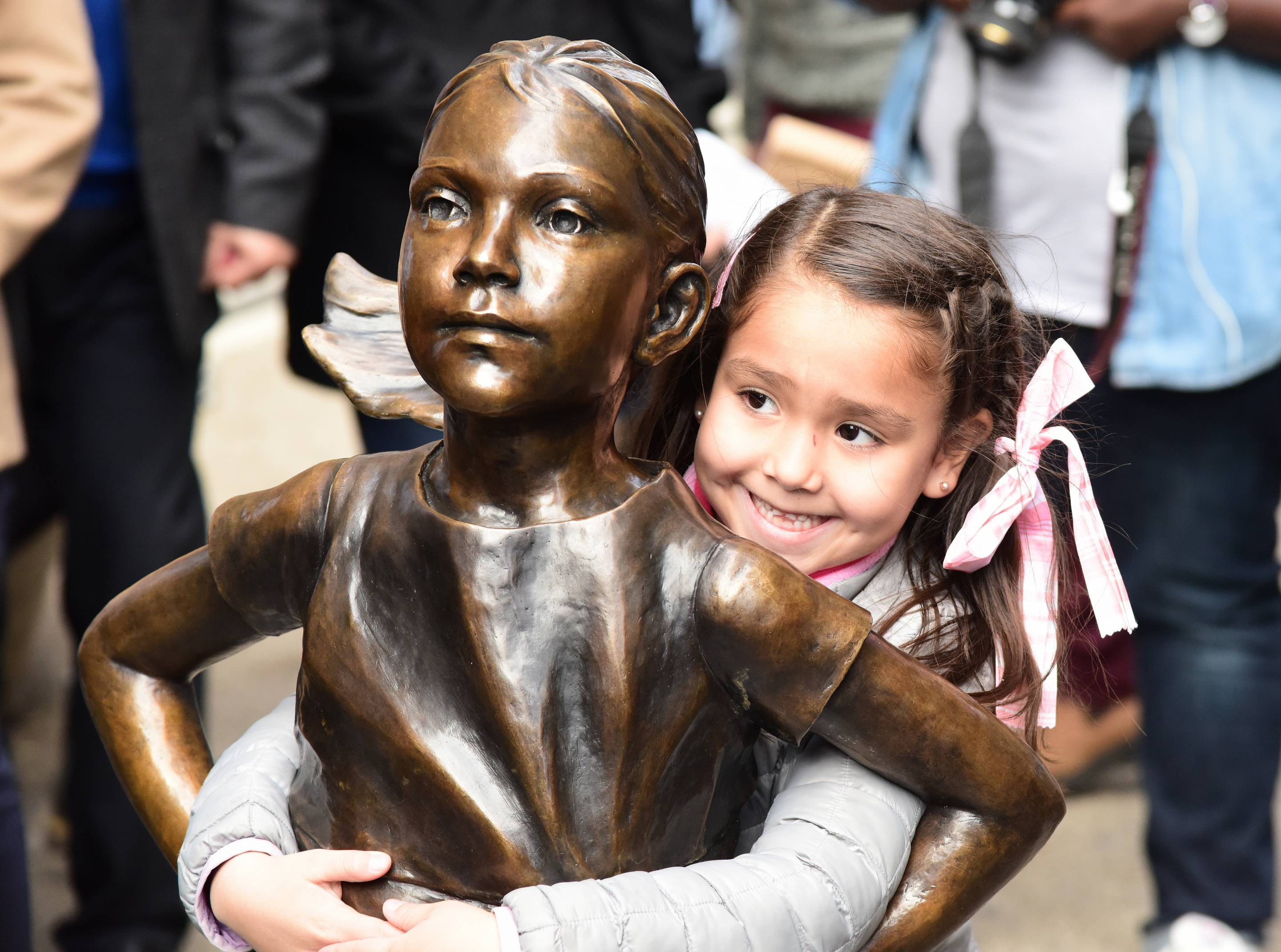 Young girl in pigtails hugs the waist of the Fearless Girl statue.