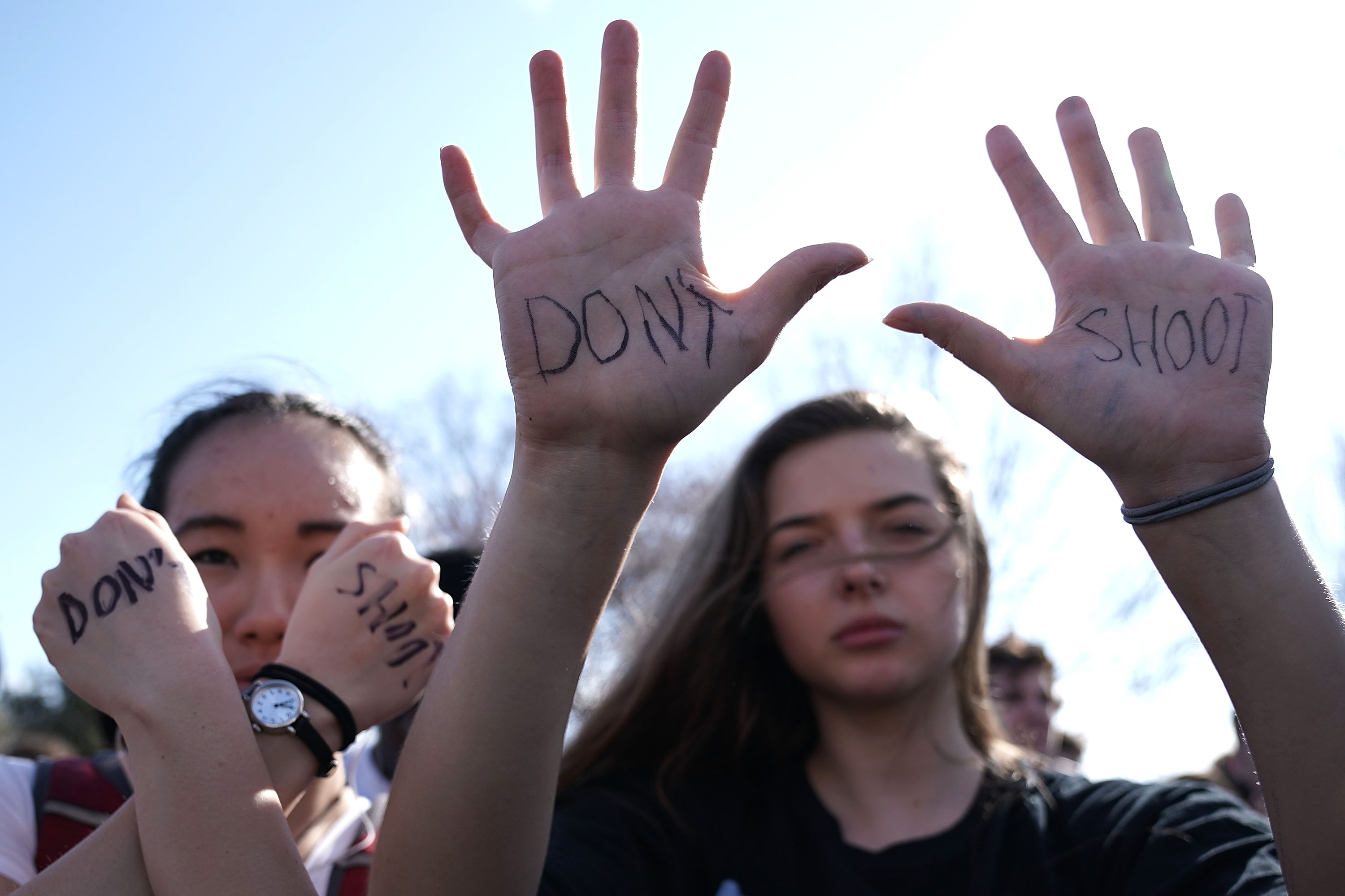 """Two female students hold up their hands, where """"don't shoot"""" has been scrawled"""