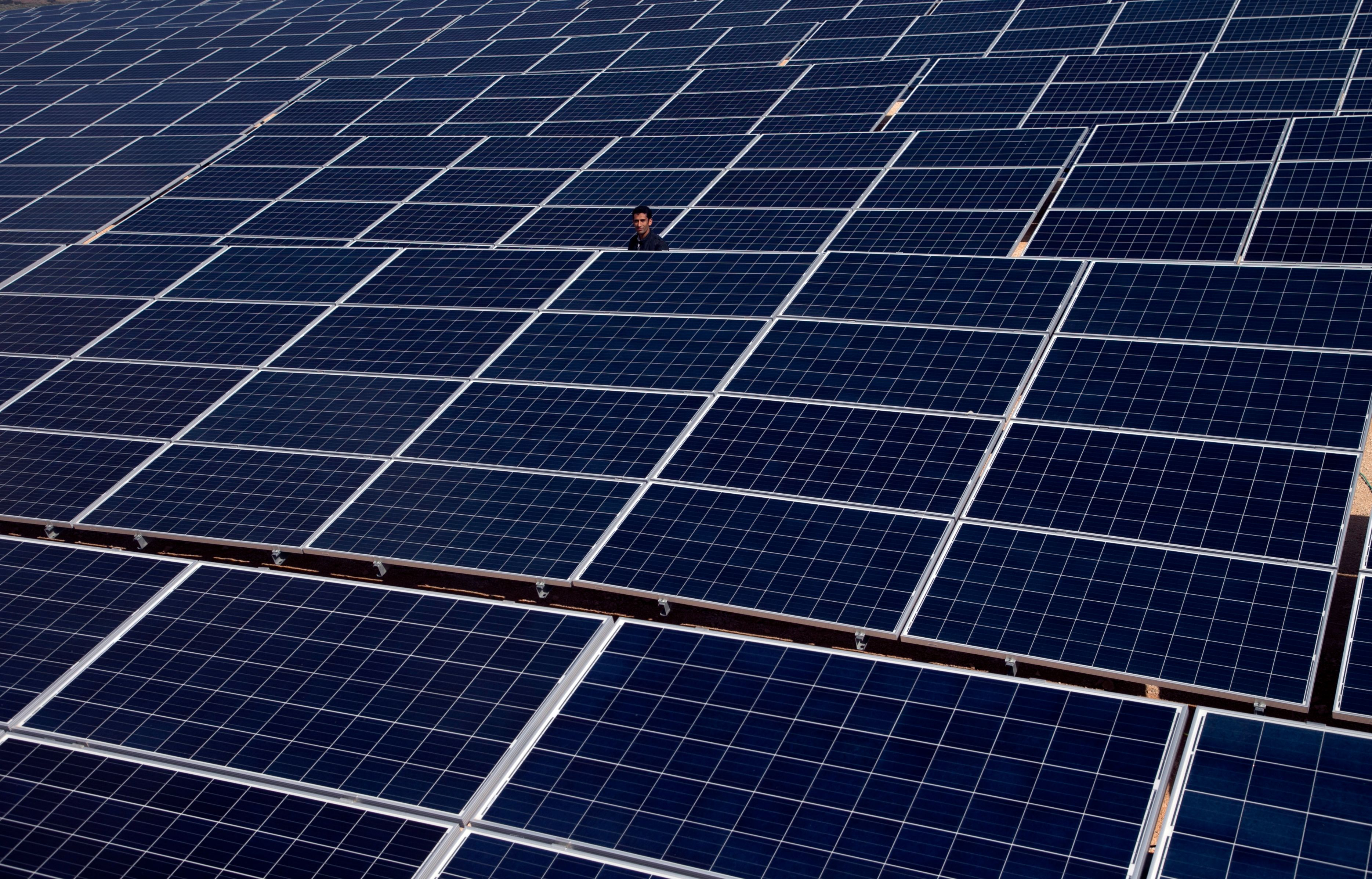 A man stand among rows of solar power panels