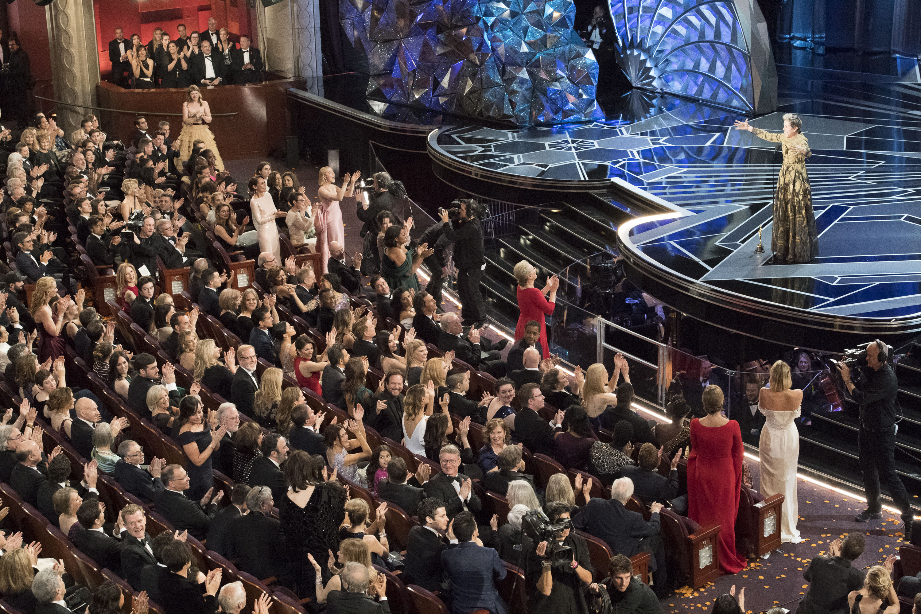 Female Oscar nominees stand in the audience as Frances McDormand delivers her Oscars speech.
