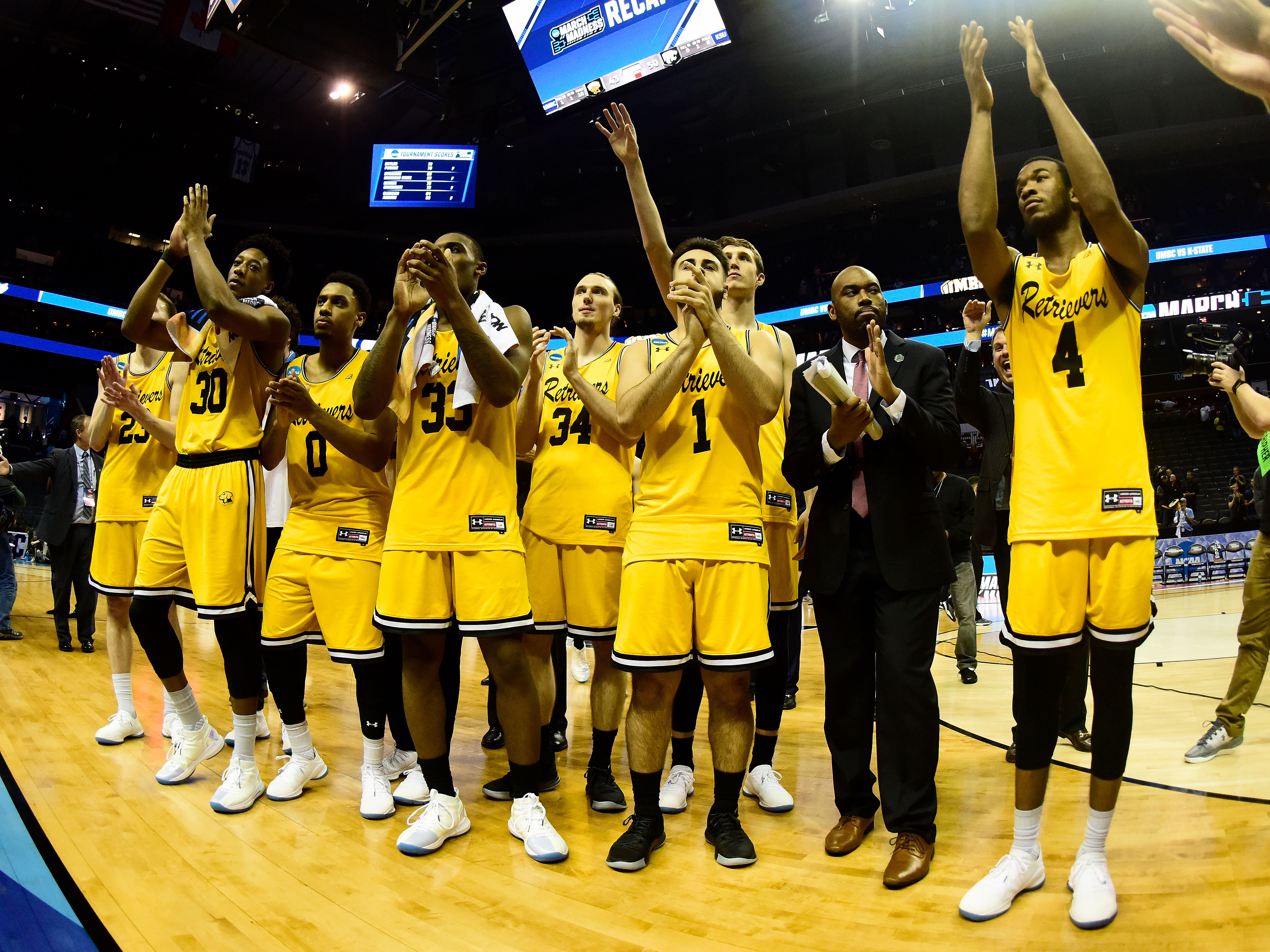 UMBC team claps on basketball court after loss to Kansas State