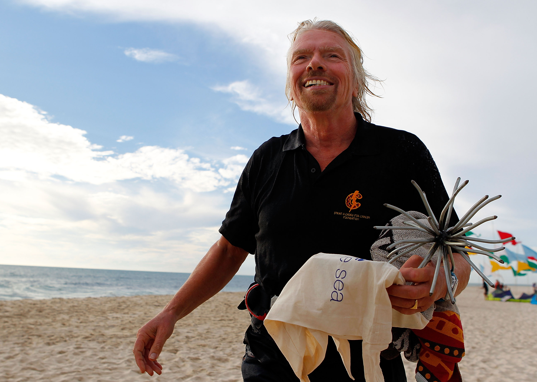 Richard Branson, Virgin founder, walks on a white sand beach.