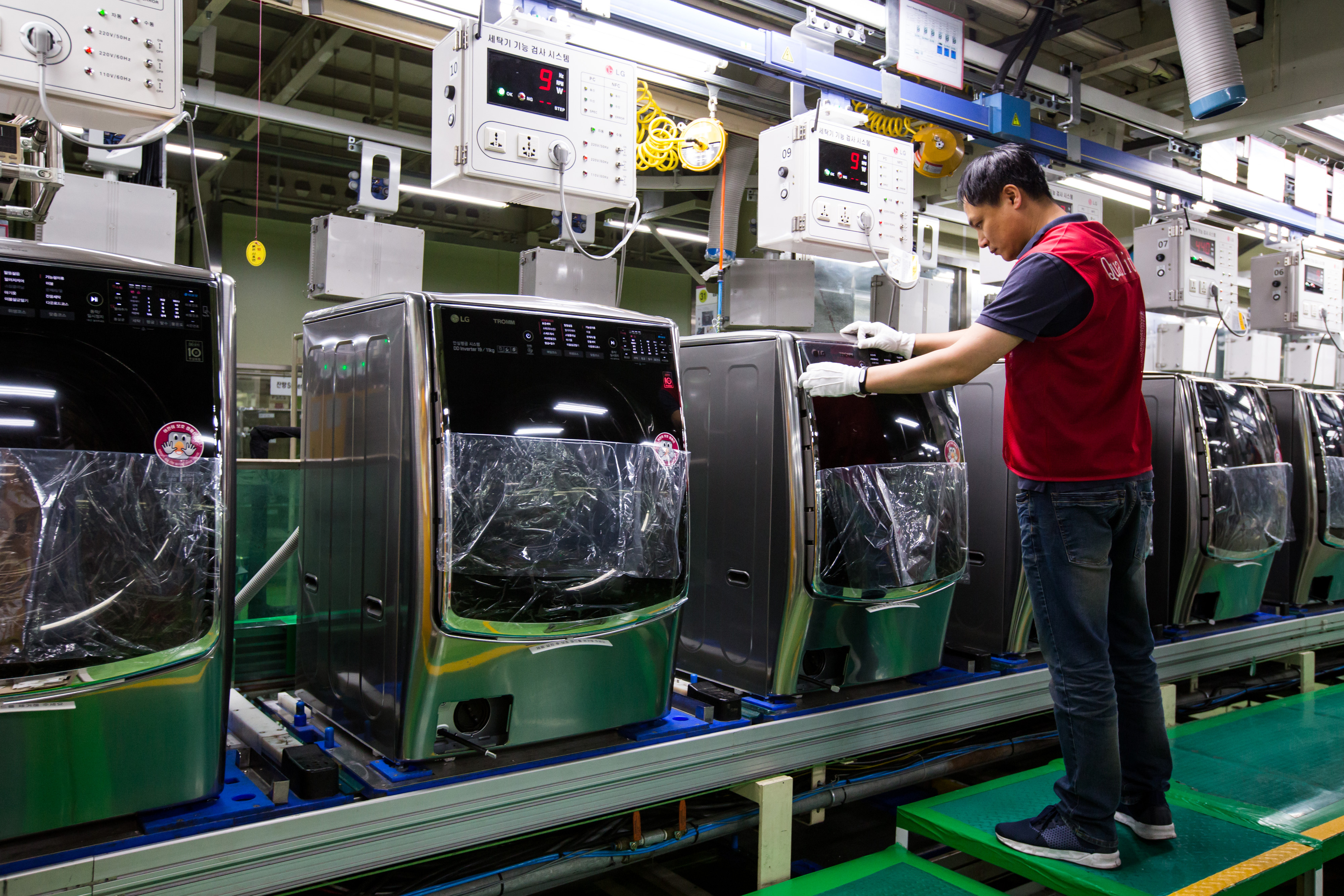 An employee attaches a sticker to an LG washing machine on production line at the company's factory in Changwon, South Korea.