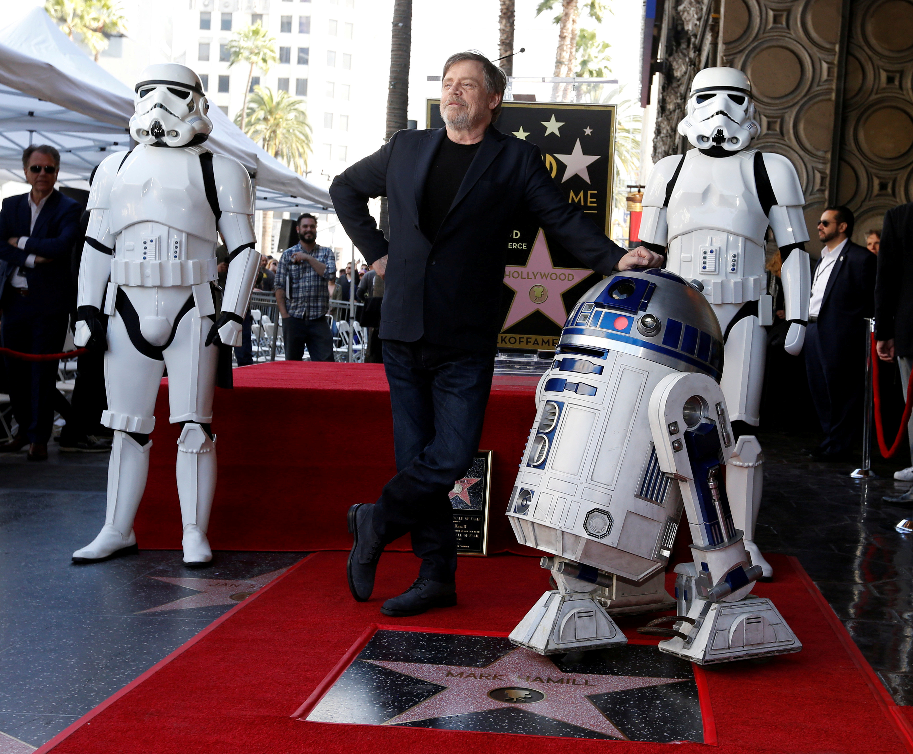 """Actor Mark Hamill poses with """"Star Wars"""" characters R2-D2 and Stormtroopers after unveiling his star on the Hollywood Walk of Fame in Los Angeles"""