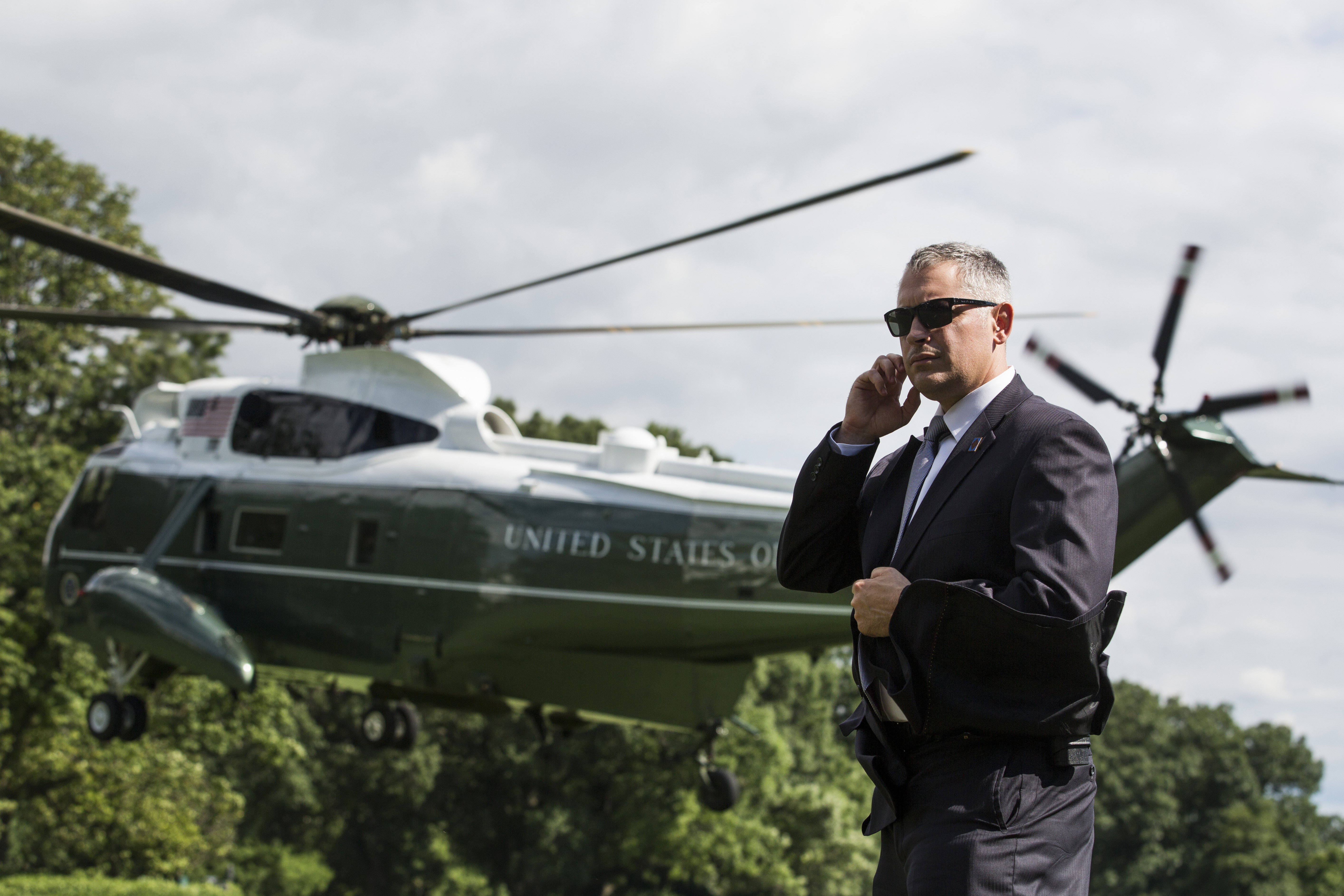 A U.S. Secret Service Agent stands as Marine One departs the White House.