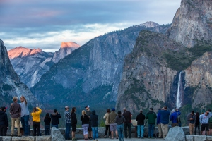 visitors take photos and enjoy the sunset overlooking the Yosemite Valley floor at sunset.